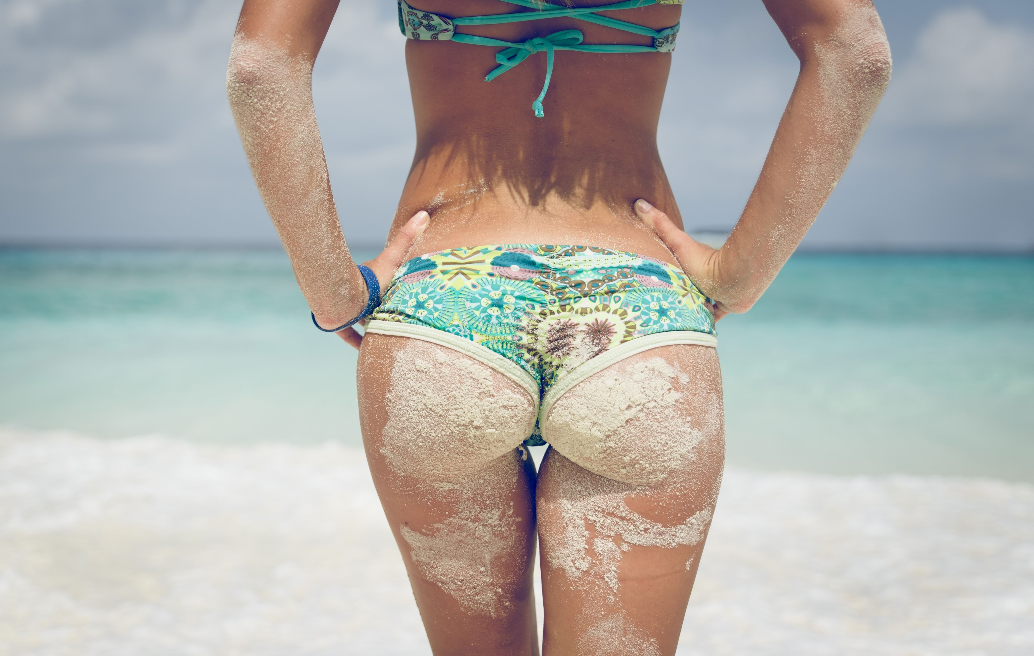 Фото Загорелая красивая попка в песке, девушка в голубых шортиках на пляже, бедра в песке, море, купальник, скачать картинку бесплатно