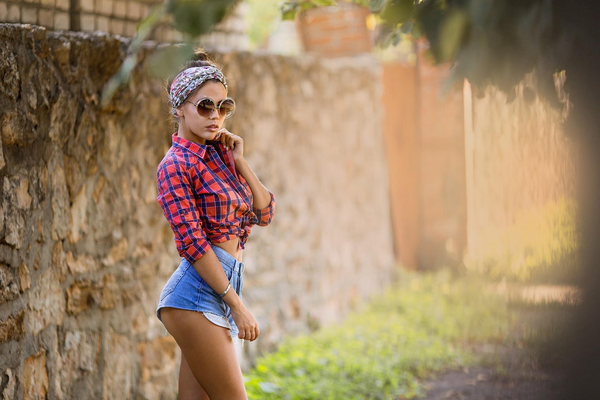 Фото Девушка гуляет в коротких джинсовых шортиках, розовая клетчатая рубашка, очки, бандана, сексуальная фигура, упругие бедра, скачать картинку бесплатно