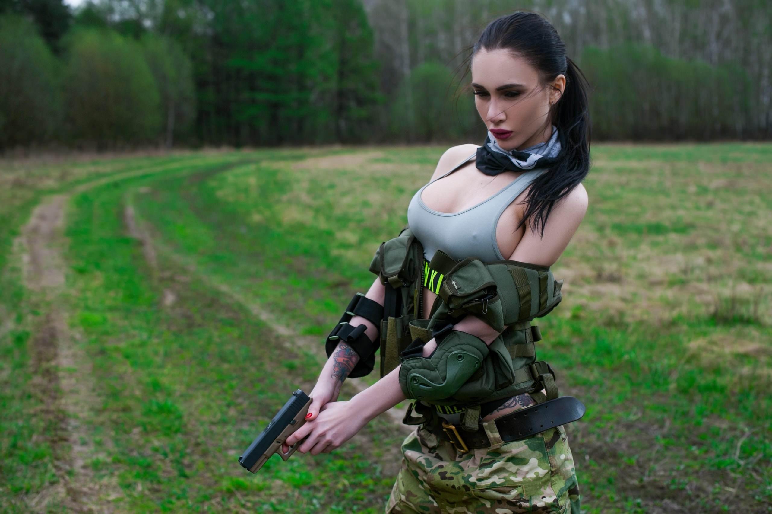 Фото Девушка в камуфляже, большая грудь в серой майке, солдат, пистолет, дорога, трава, сексапильная брюнетка в военной форме, скачать картинку бесплатно