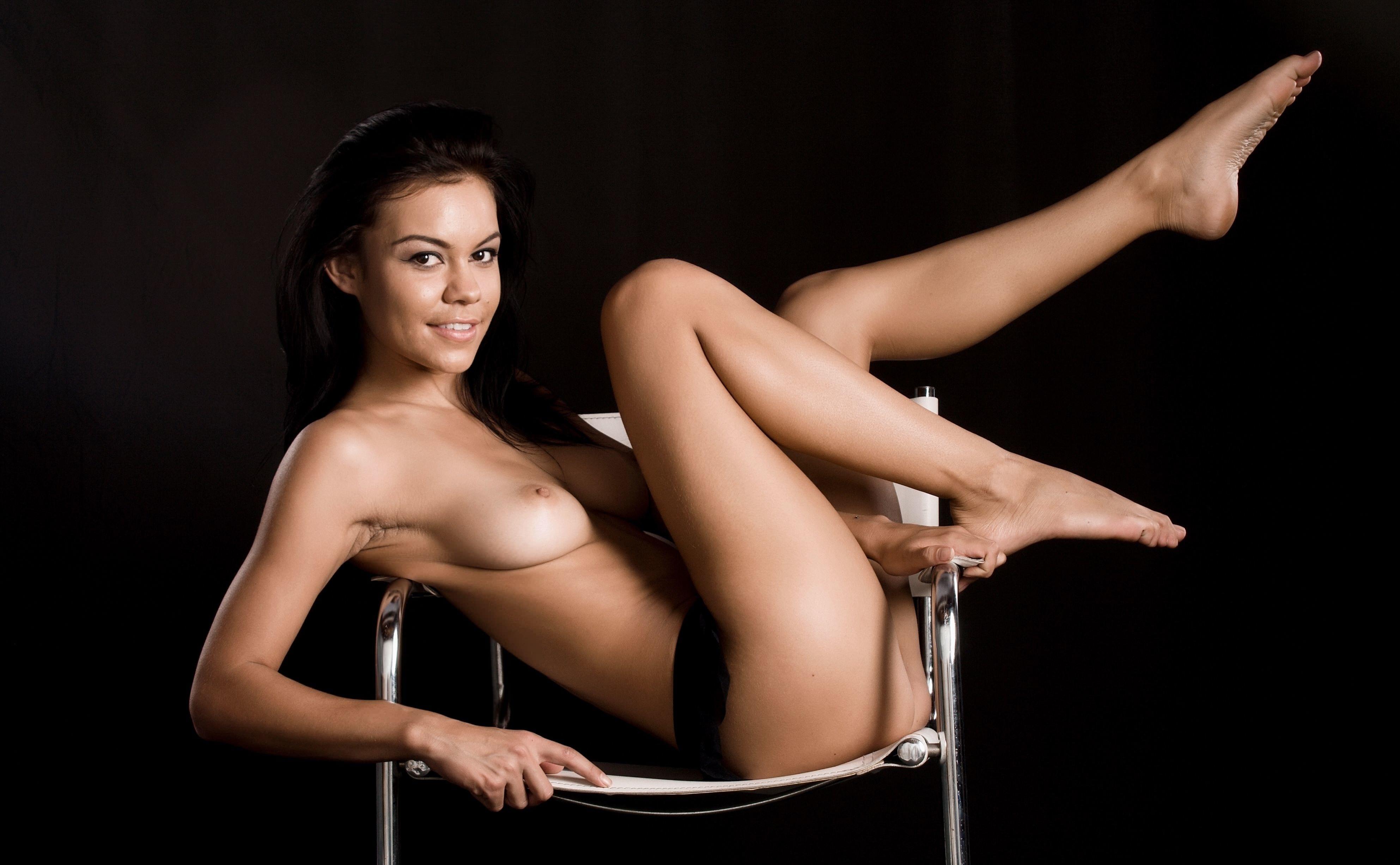 Фото Обнаженная брюнетка на стуле, черный фон, скачать картинку бесплатно