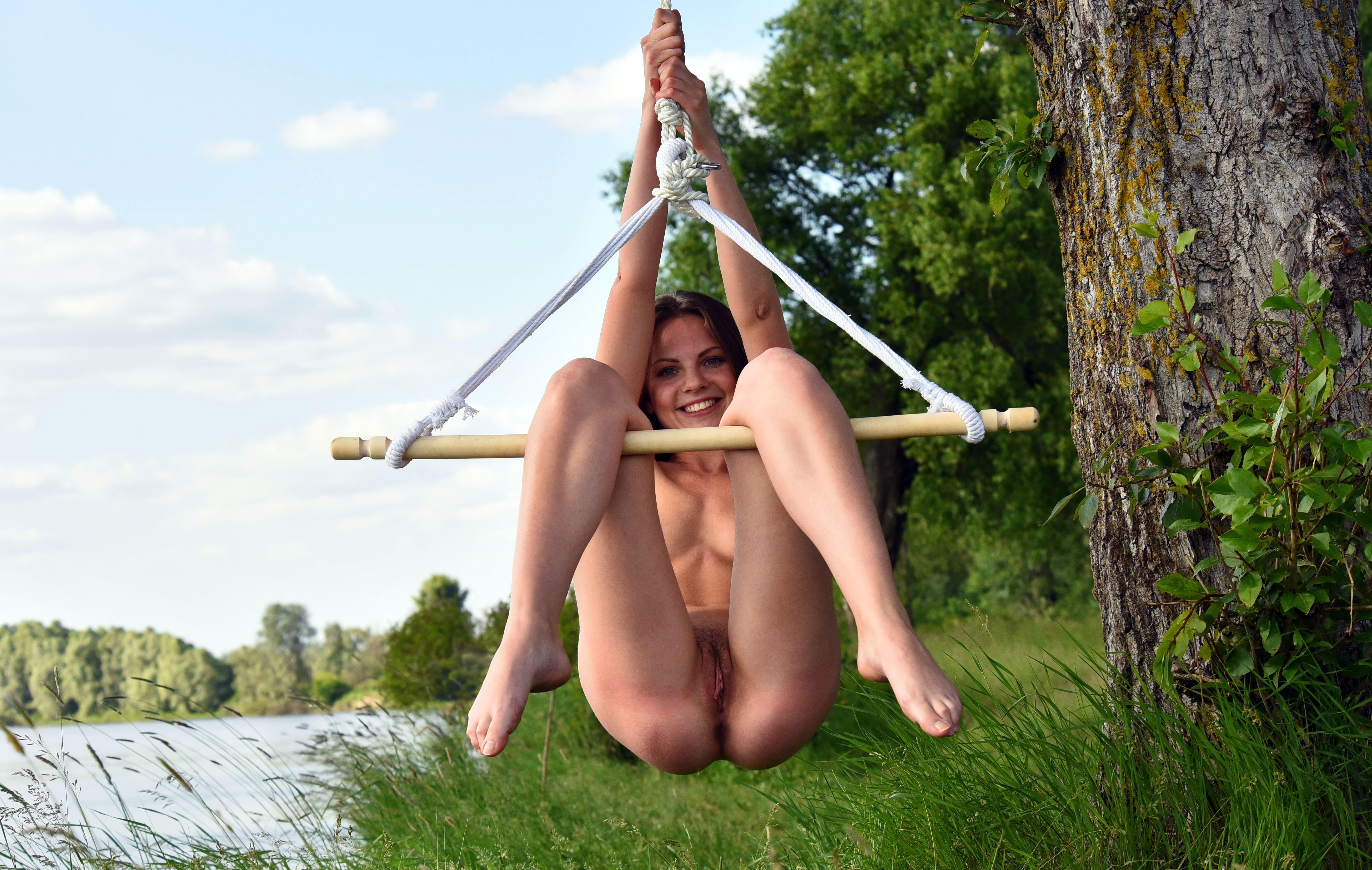 Фото Голая девушка качается на самодельных качелях у озера, голая попка над зеленой травой, скачать картинку бесплатно