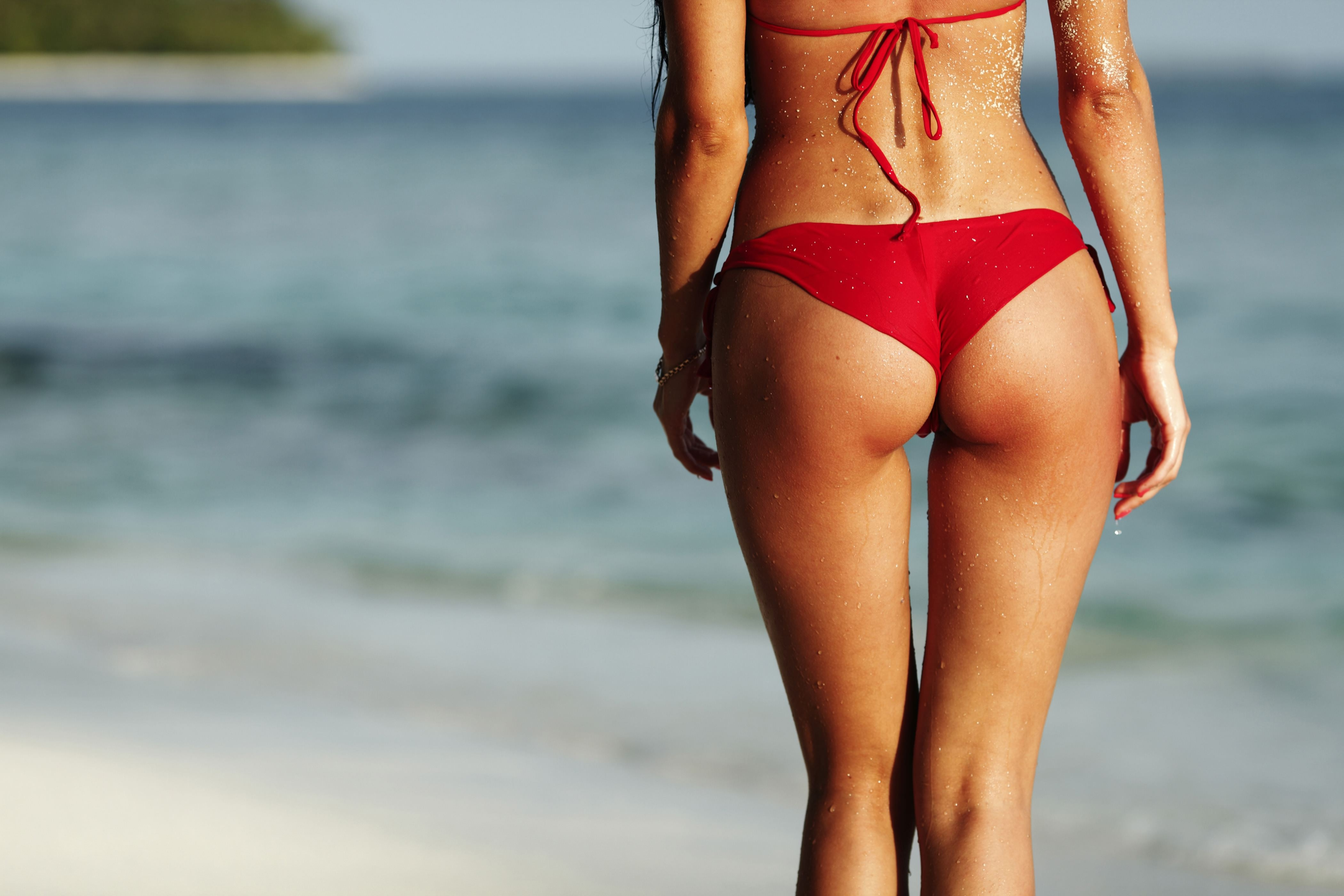 Фото Загорелые красивые ножки, упругая попка в красных трусиках, девушка в купальнике гуляет вдоль берега, скачать картинку бесплатно