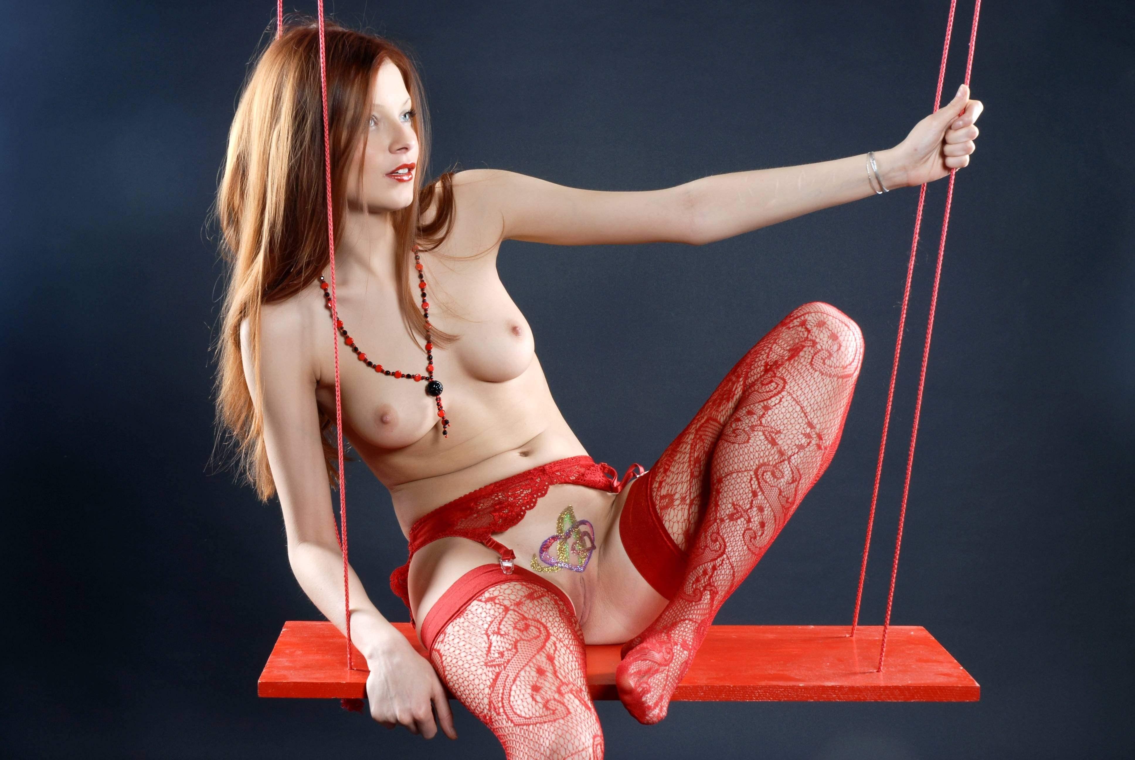Фото Девушка качается на качелях, красные узорчатые чулки, тату на лобке, обнаженная грудь, бритая татуированная киска между ног, скачать картинку бесплатно