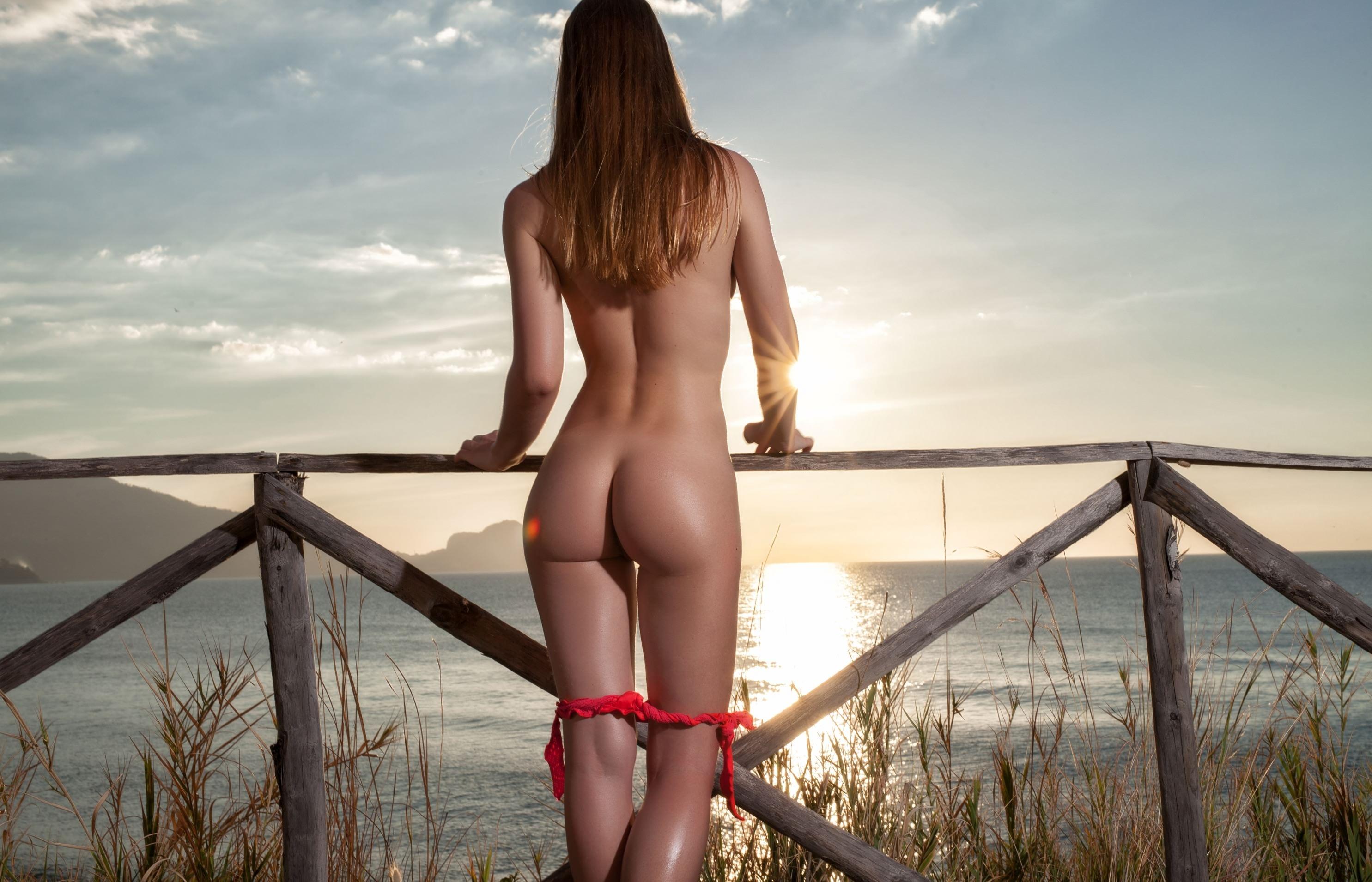 Фото Девушка стянула розовые трусики до колен, смотрит на горизонт, закат, море, забор, классная попа, скачать картинку бесплатно