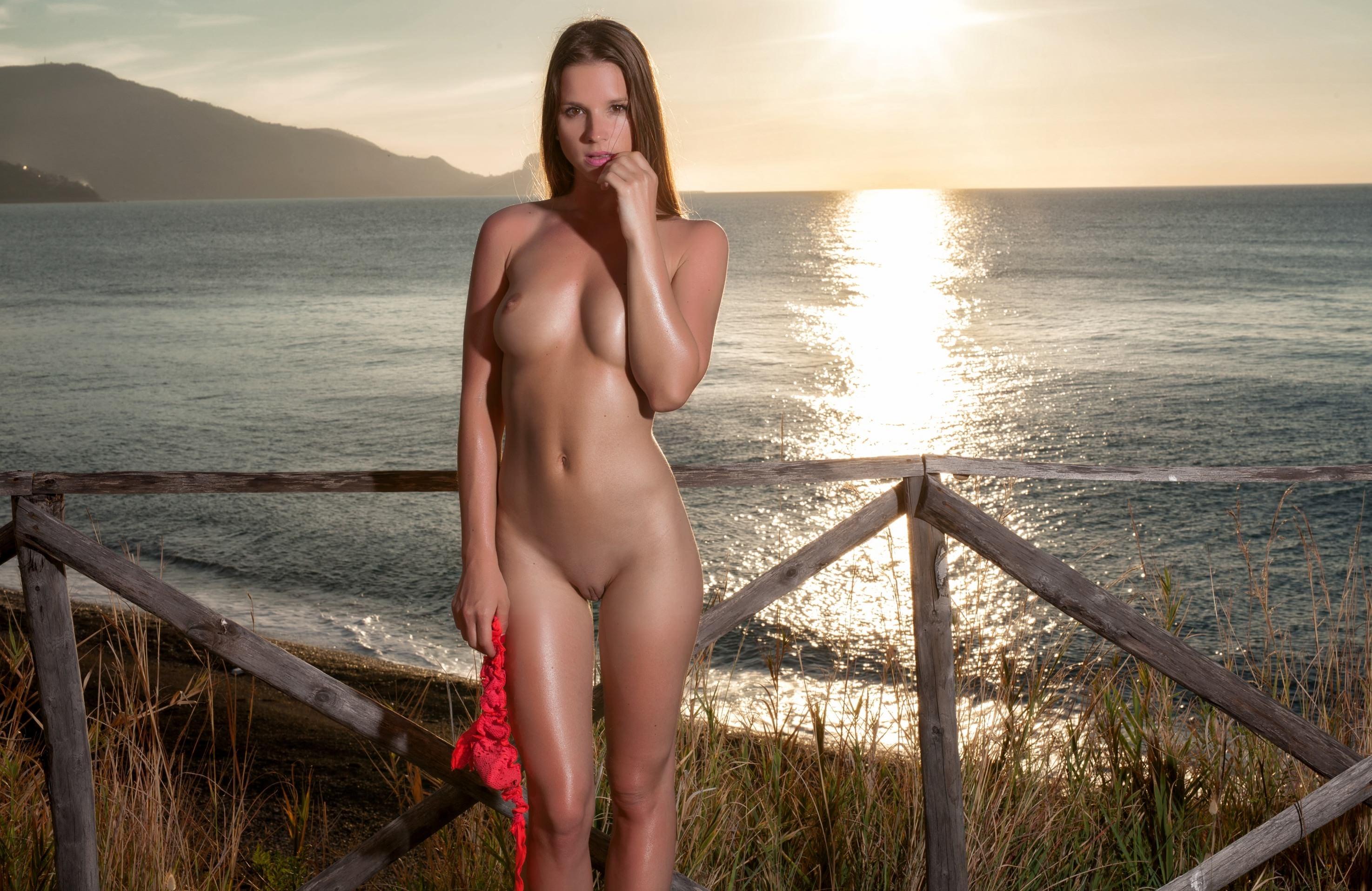 Фото Обнаженная девушка держит в руке красные трусики, море, закат, забор, соблазн, сексуальное тело, скачать картинку бесплатно