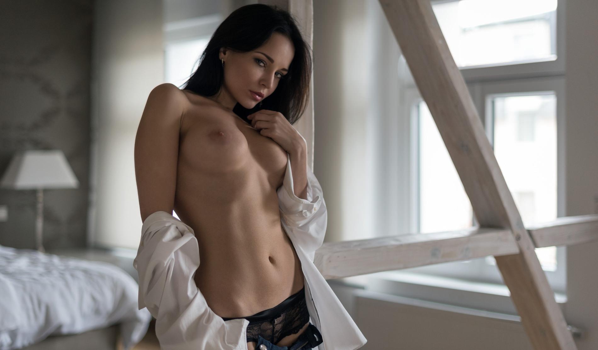 Фото Соблазнительная девушка эротично оголила грудь, ласкает сиську, сняла рубашку, животик, пупок, спальня, соблазнительный взгляд, скачать картинку бесплатно