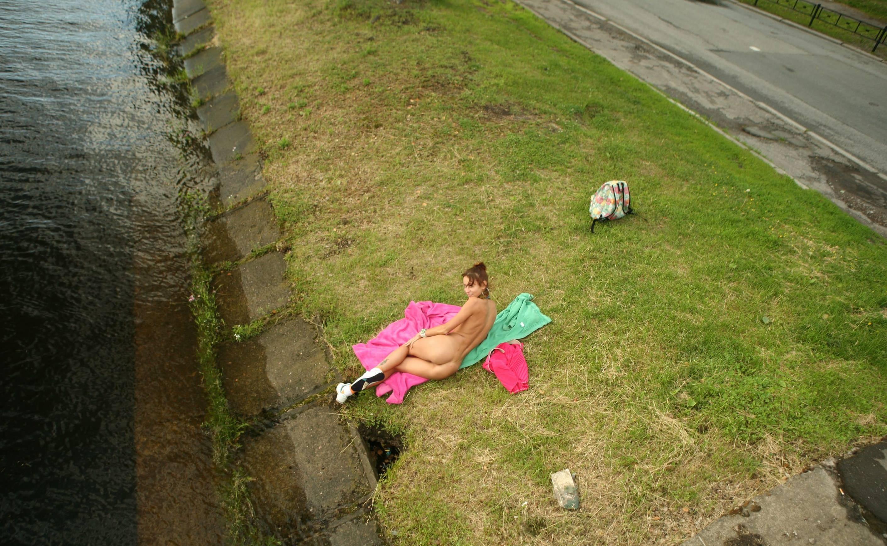 Фото Голая девушка разлеглась на городской набережной, скачать картинку бесплатно