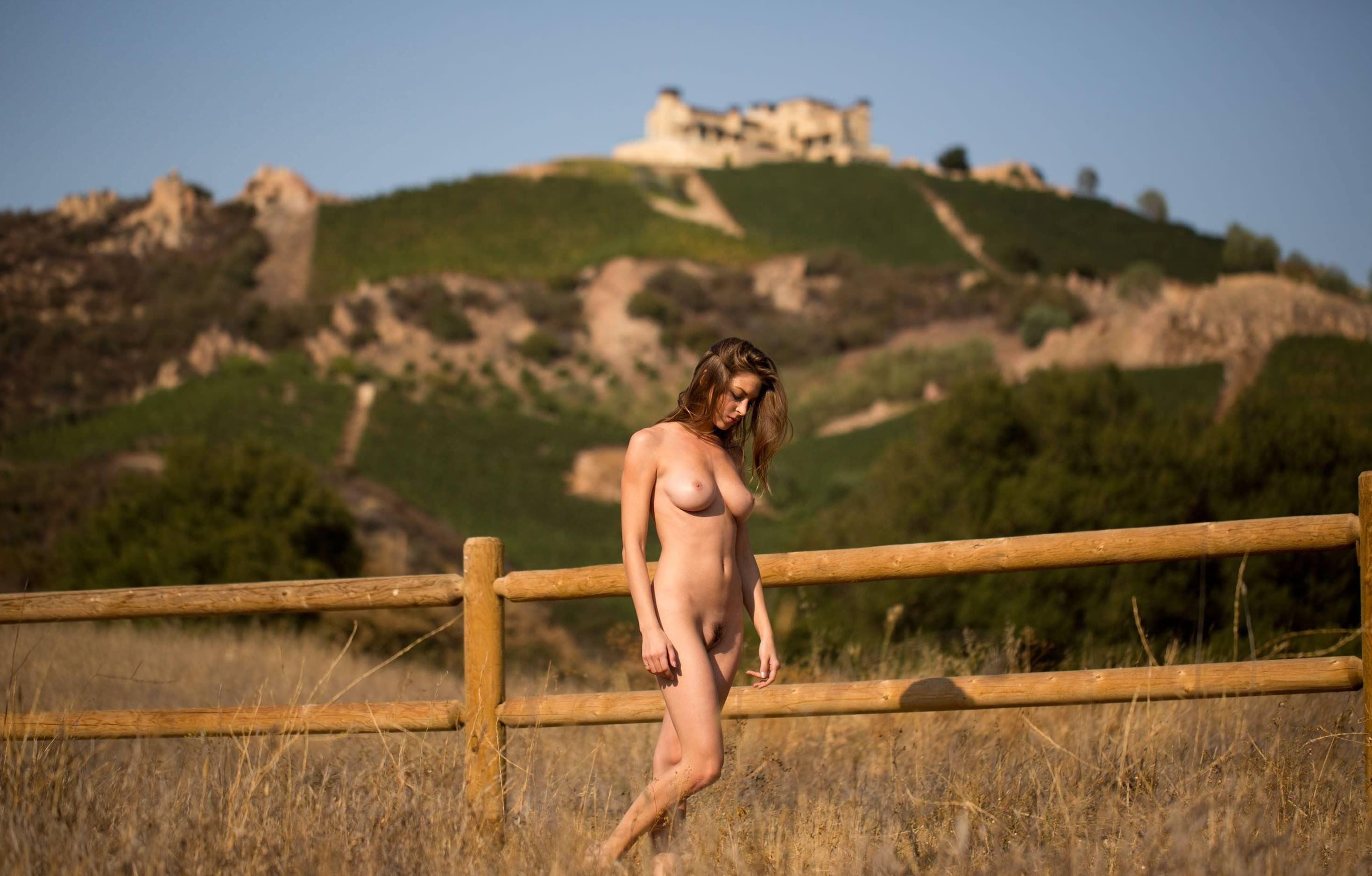 Фото Обнаженная девушка шагает вдоль забора в деревне, поле, трава, скачать картинку бесплатно