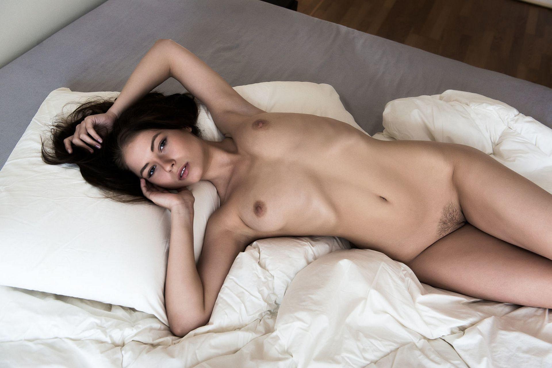 Фото Голая брюнетка, небритый лобок, постель, подушки, скачать картинку бесплатно