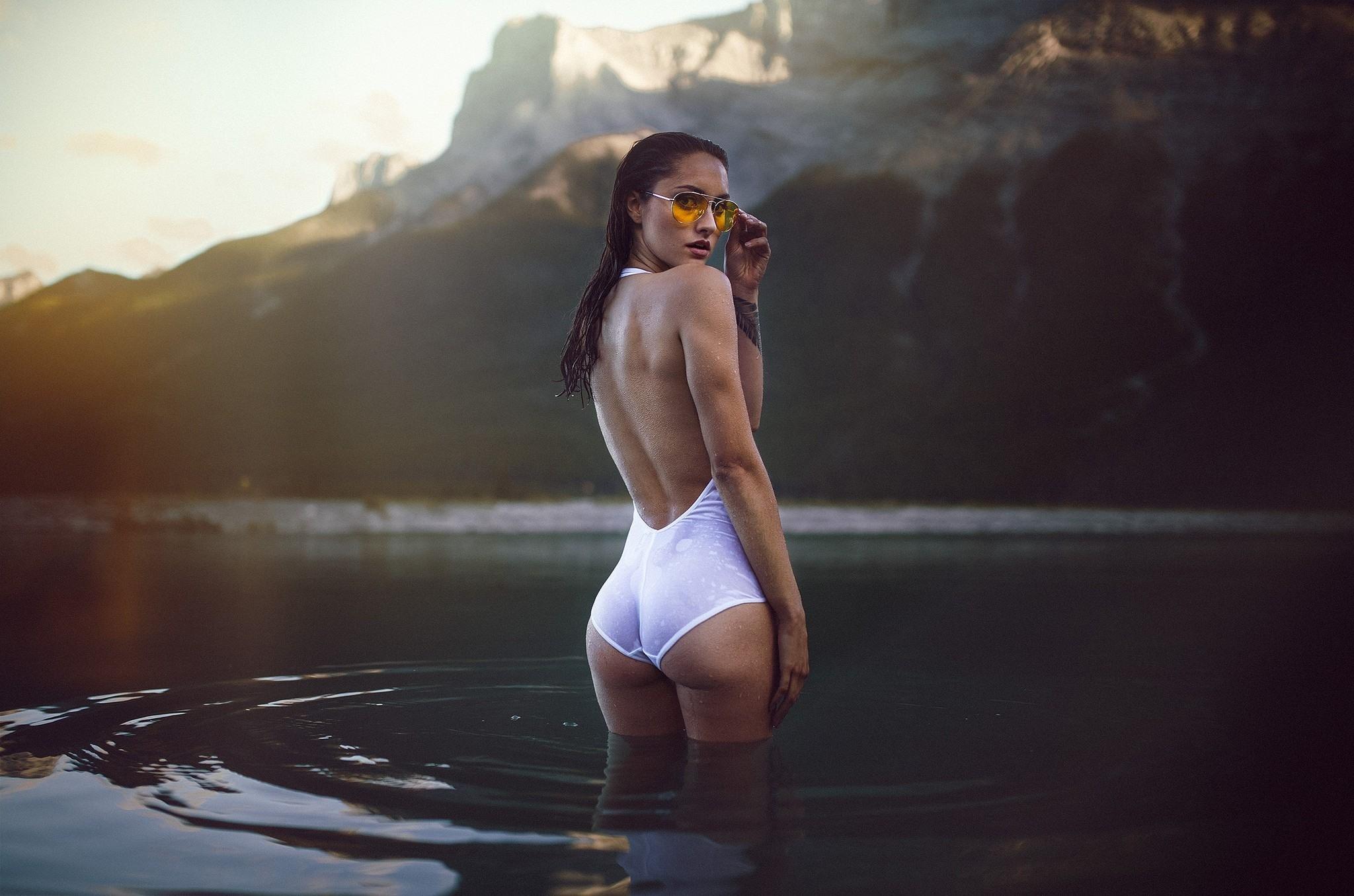 Фото Девушка в белом купальнике, озеро, по полено в воде, мокрая попка, очки, гора, скачать картинку бесплатно