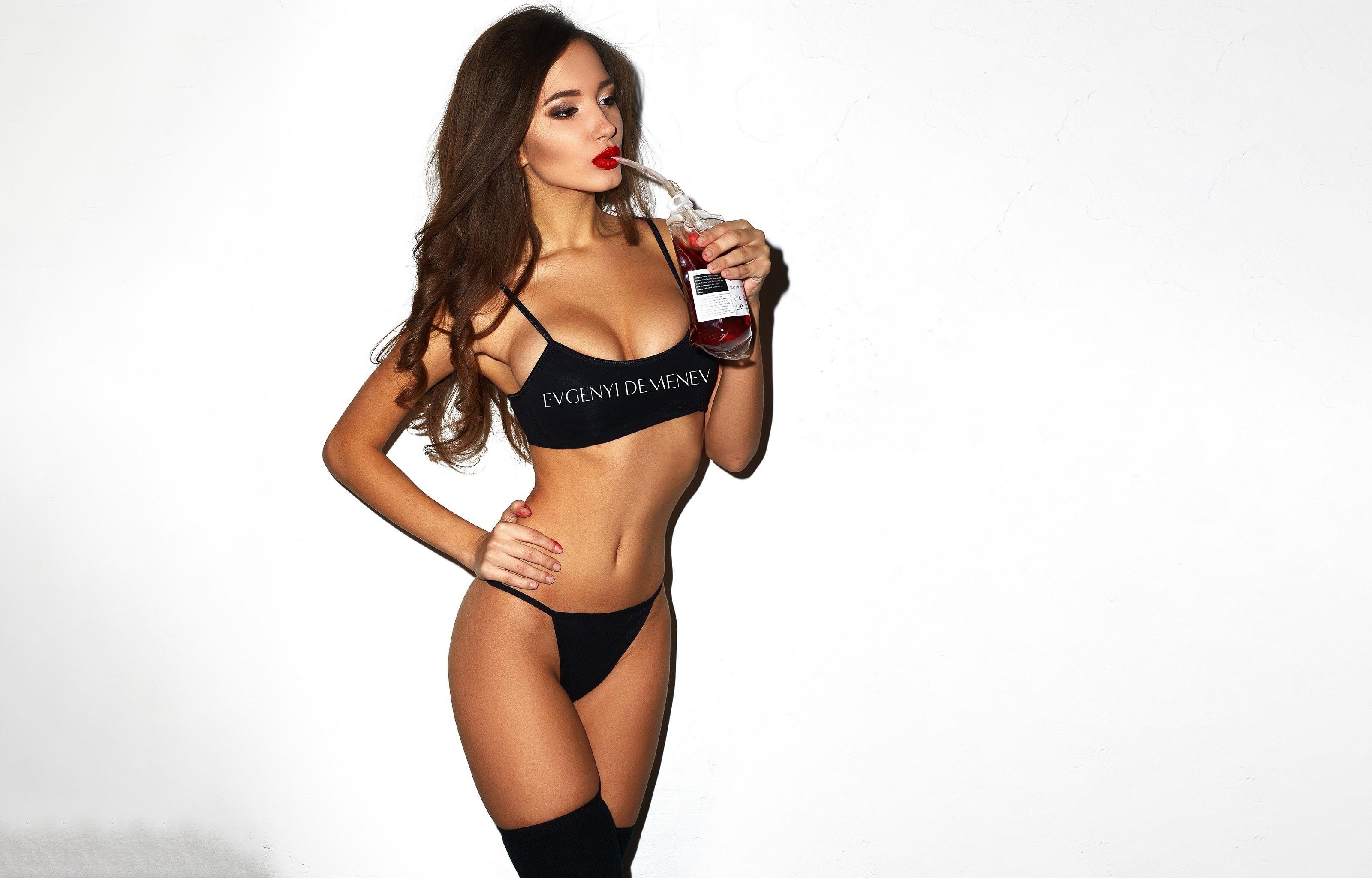 Фото Сексуальная девушка сосет кровь из донорского пакета, черный лифчик, трусики, гольфы, классная грудь, секси брюнетка, красные губки, скачать картинку бесплатно