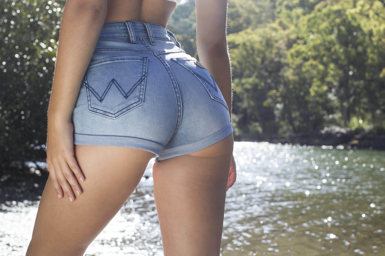 Фото Красивая упругая попка в обтягивающих джинсовых шортиках, девушка у реки, красивые подтянутые бедра, скачать картинку бесплатно