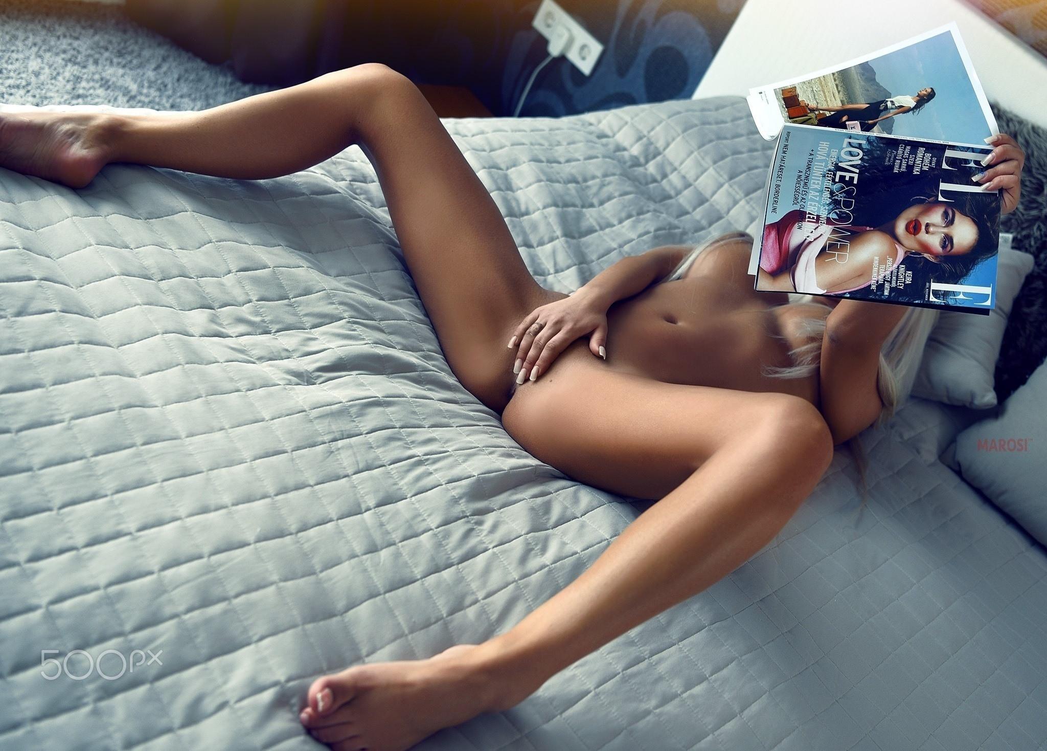 Фото Голая девушка смотрит эротический журнал и ласкает писю в кровати, развела ножки, рука между ног, белокурая возбужденная девчонка в постели, сексуальные ножки, скачать картинку бесплатно
