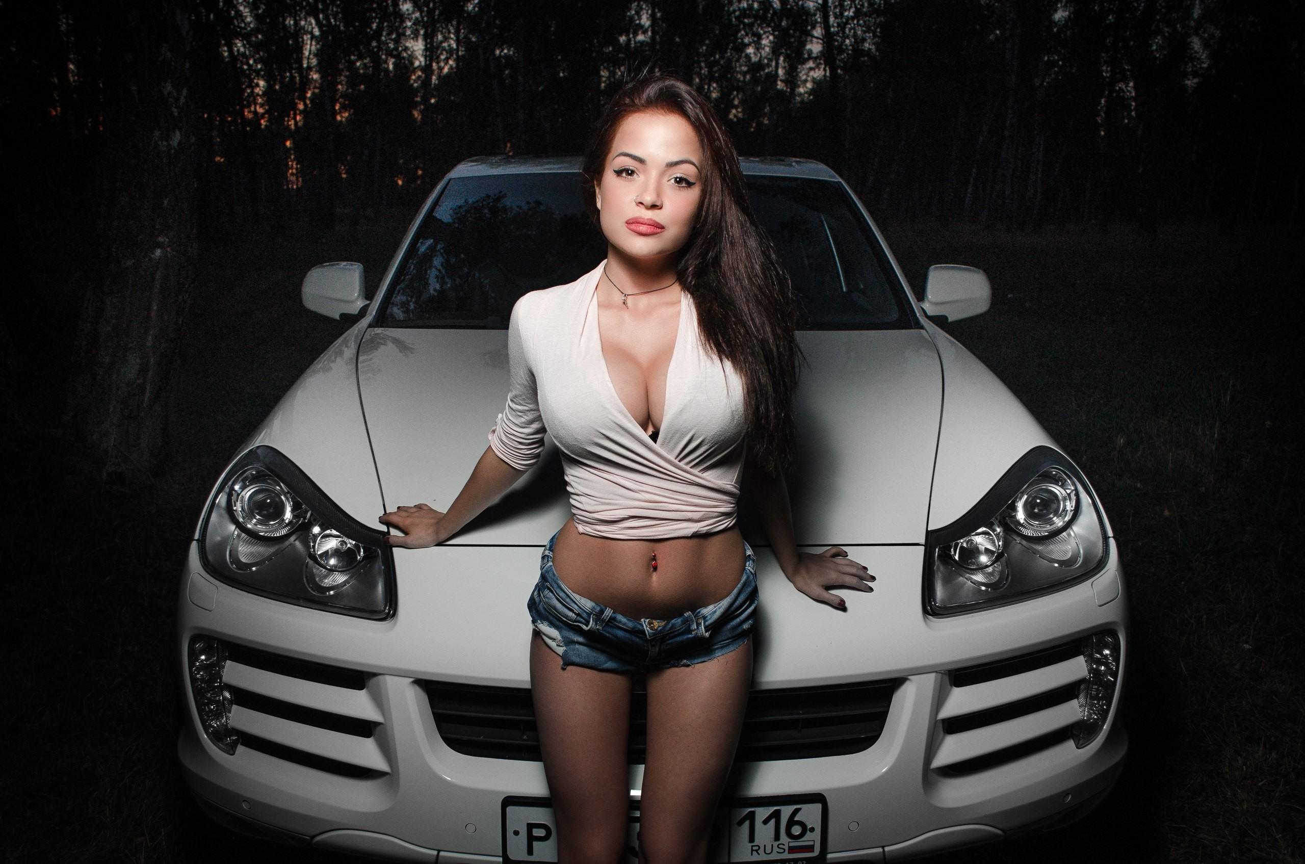 Фото Красивая девушка в коротеньких шортиках и белой блузке прислонилась попой к капоту белого авто ночью в лесу, большая грудь, пупок, секси брюнетка, скачать картинку бесплатно