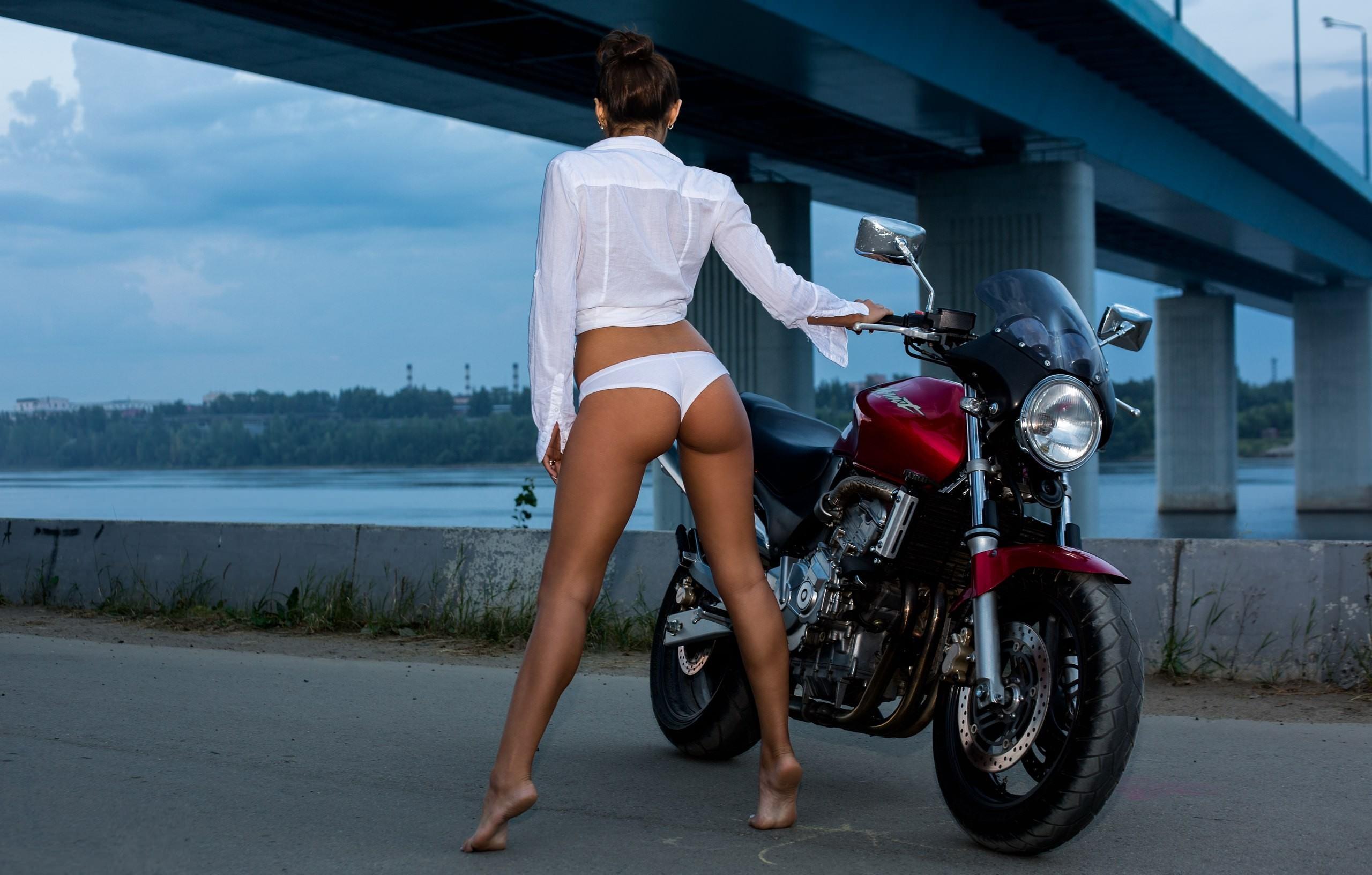 Фото Девушка в белых трусиках и рубашке встала на носочке возле мотоцикла на дороге, загорелые сексуальные ножки, упругая попка, мост, скачать картинку бесплатно