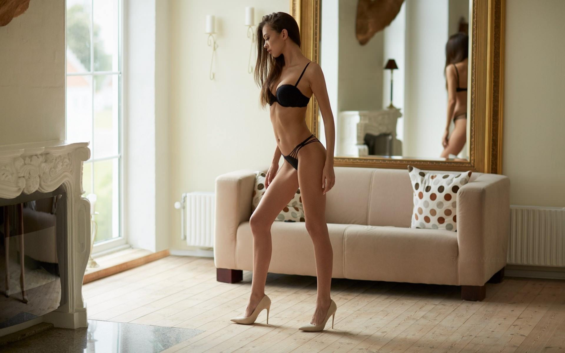 Фото Длинноногая девушка в черном нижнем белье и на каблуках в комнате, скачать картинку бесплатно