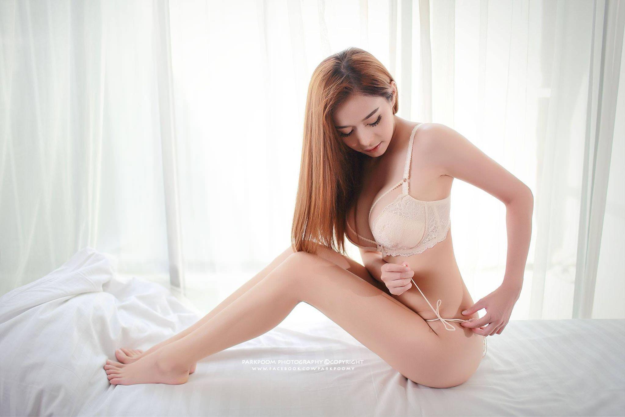 Фото Сексуальная рыжеволосая азиатка поправляет трусики, нежные ножки, белоснежная постель, скачать картинку бесплатно