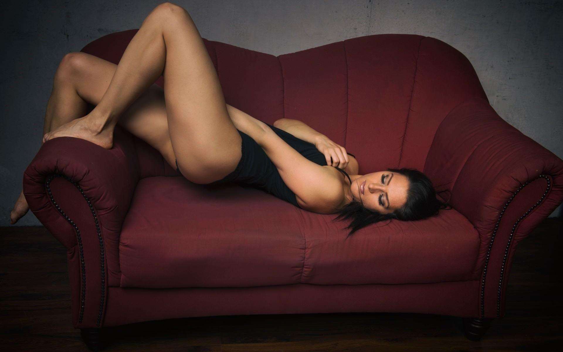 Фото Сексапильная брюнетка в черной майке изгибается на бордовом диване, упругие бедра, скачать картинку бесплатно