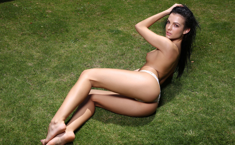 Фото Сексуальная брюнетка в трусиках лежит на зеленом газоне, скачать картинку бесплатно
