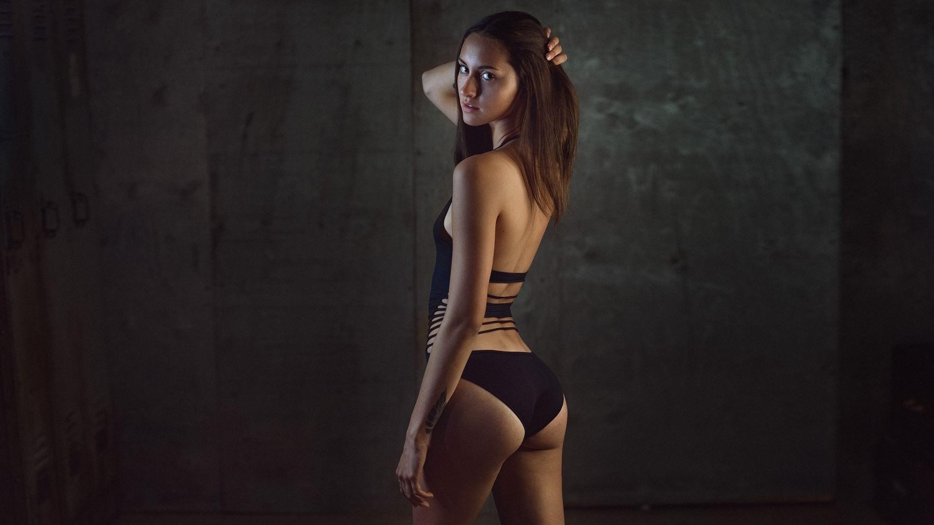 Фото Девушка в черном купальнике, милая попка, поправляет волосы в темноте, скачать картинку бесплатно