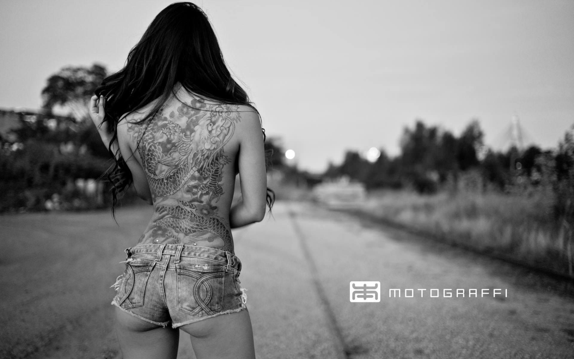 Фото Вся спина в тату, брюнетка в коротких шортиках на дорогу, скачать картинку бесплатно