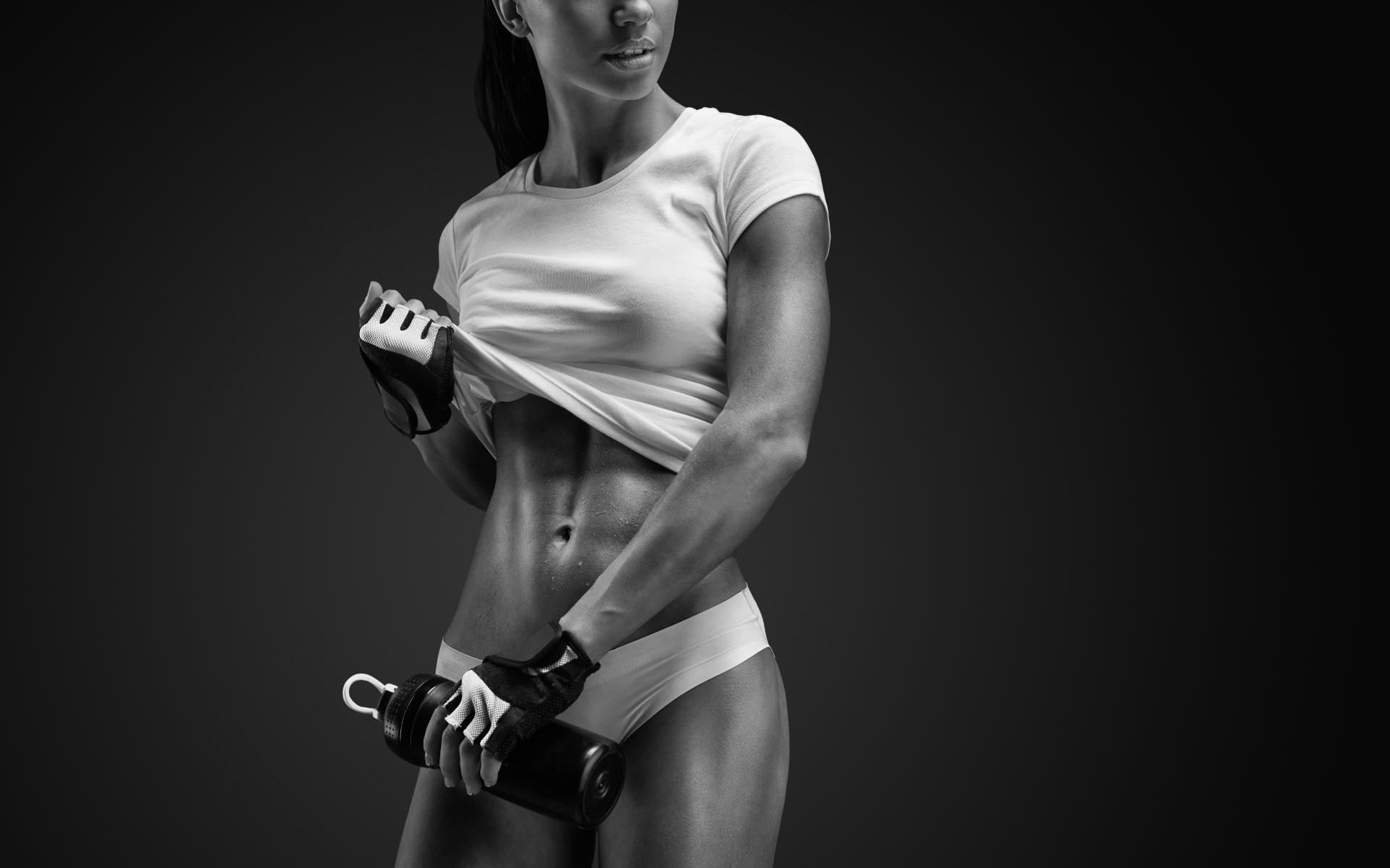 Фото Спортивная девушка в перчатках после тренировки с бутылкой энергетика стягивает белую футболку, пресс, скачать картинку бесплатно