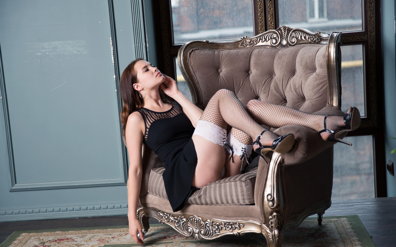 Фото Девушка в сетчатых чулочках и черном платье лежит эротично в кресле, видно трусики, сексуальные бедра, скачать картинку бесплатно