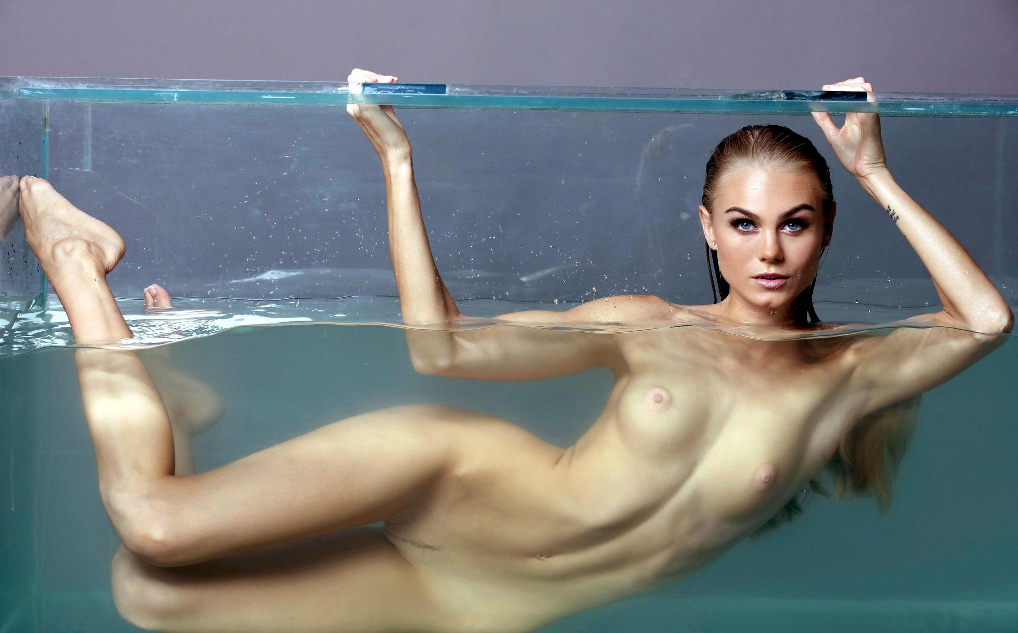 Фото Обнаженная девушка купается в большом аквариуме, красотка в воде без одежды, скачать картинку бесплатно