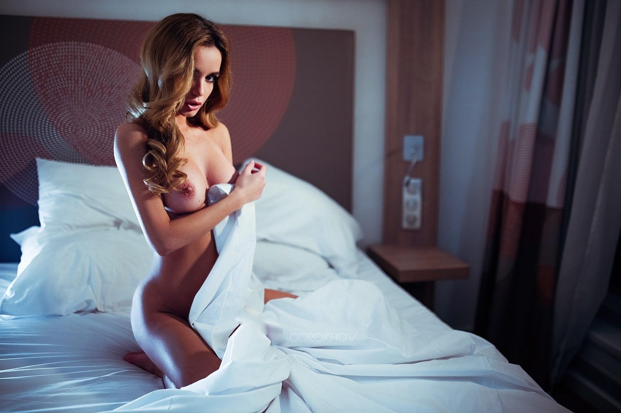 Фото Соблазнительная обнаженная девушка укрывается одеялом в постели на коленях, скачать картинку бесплатно