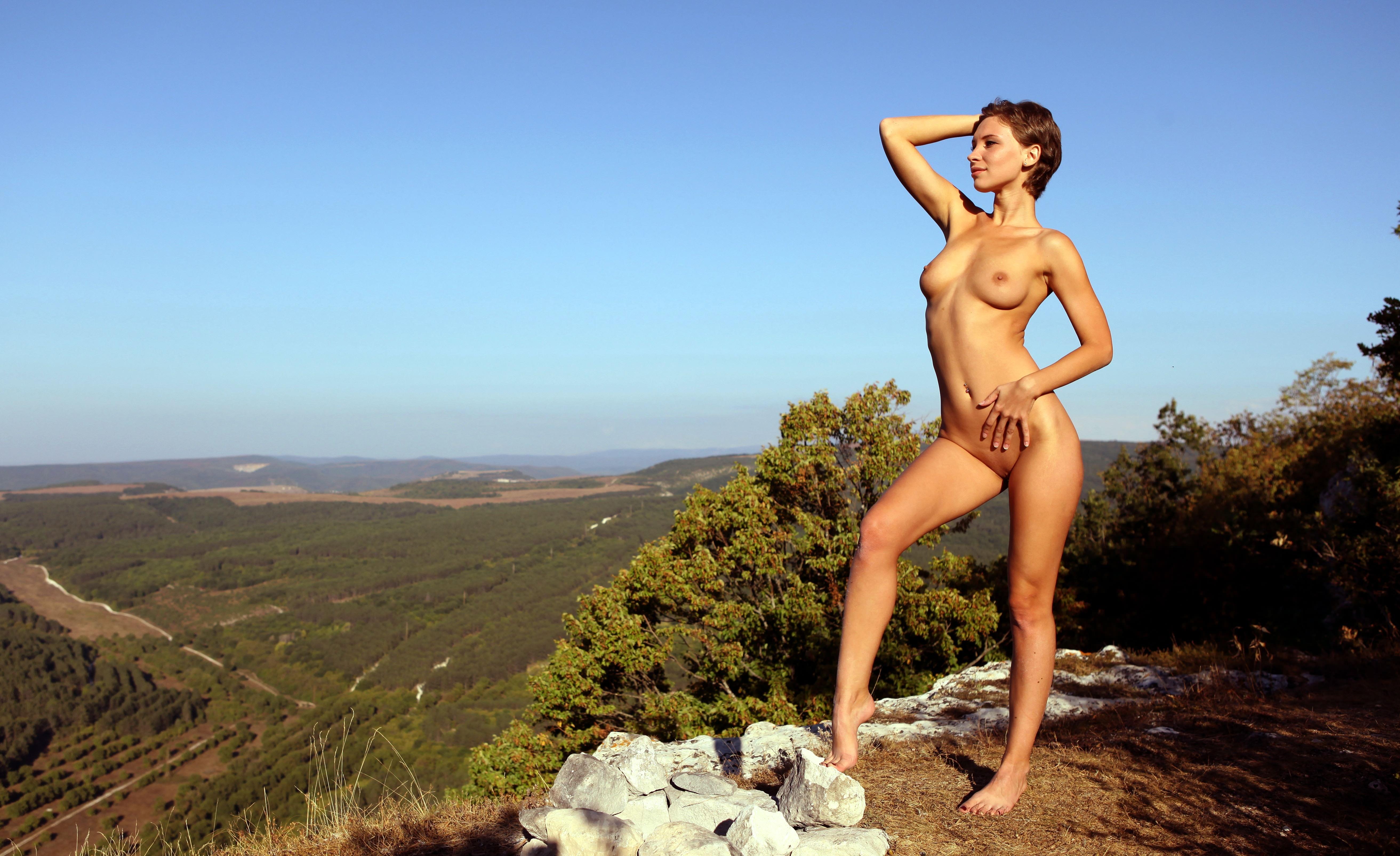 Фото Голая девчонка любуется видом с возвышенности, бескрайние зеленые поля, сексуальная тело, голубое небо, скачать картинку бесплатно