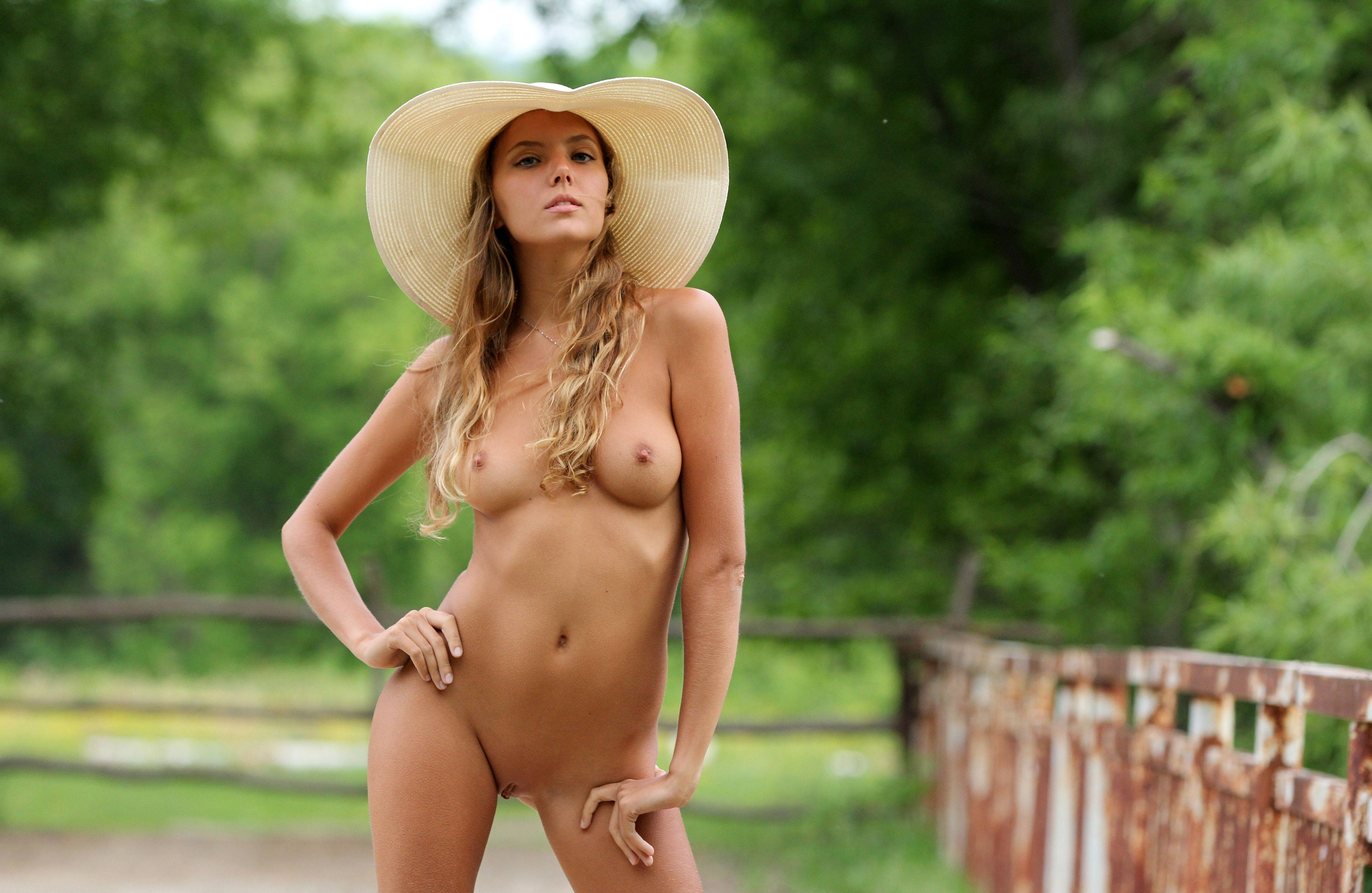 Фото Обнаженная молоденькая красотка в соломенной шляпке, забор, поле, скачать картинку бесплатно