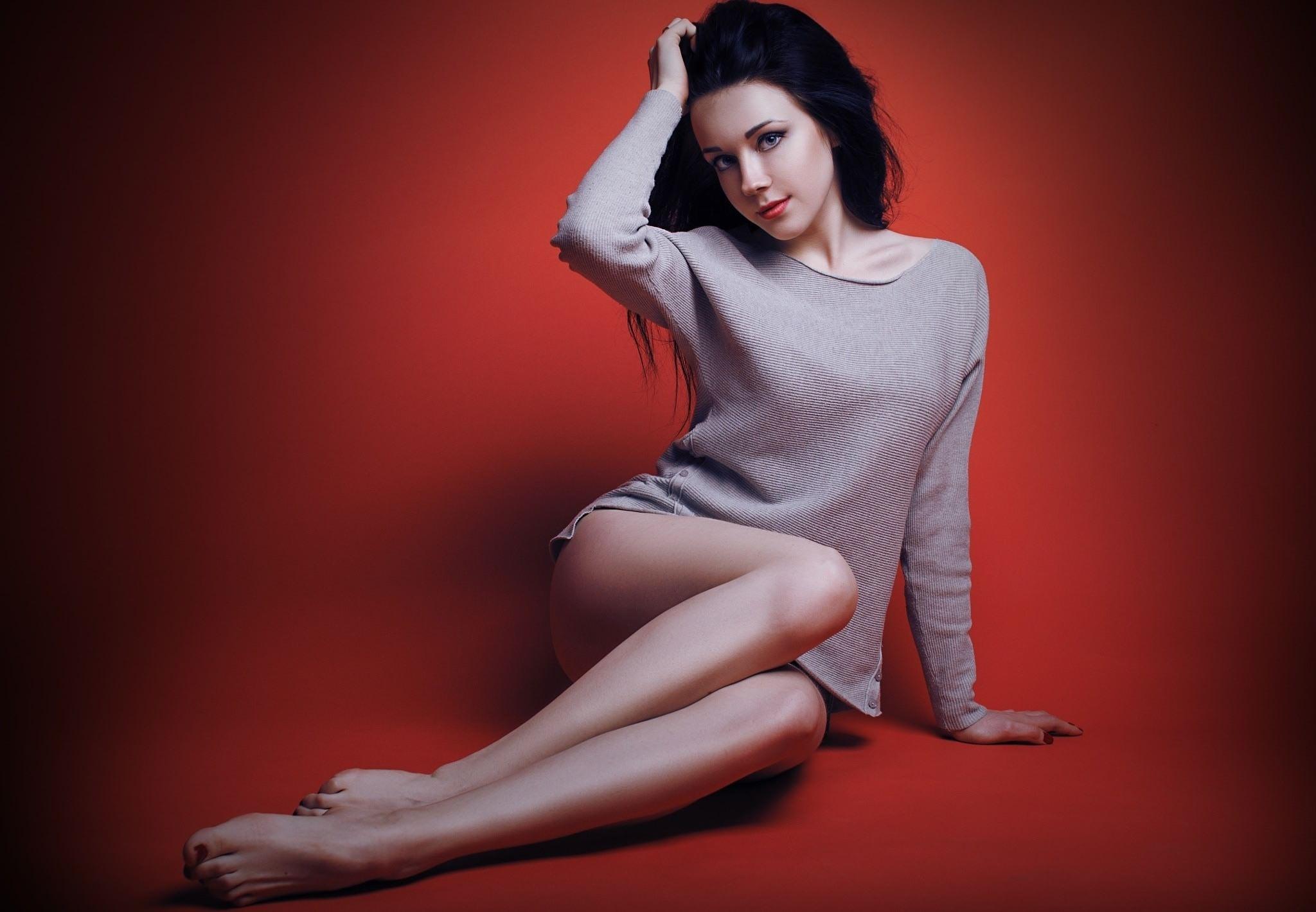Фото Молодая девчонка в серой кофте, черные волосы, красивые нежные ножки, красный фон, скачать картинку бесплатно