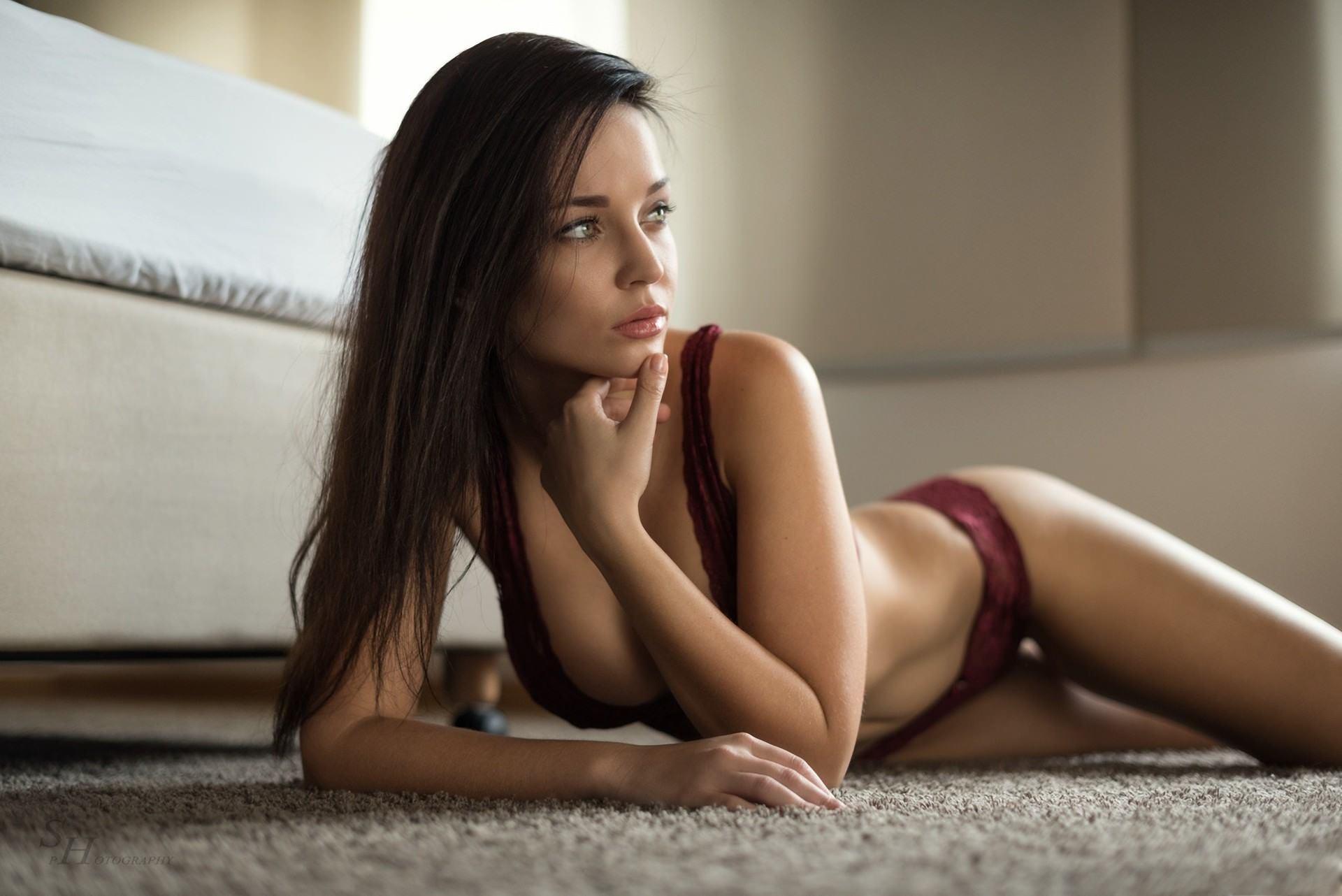Фото Красивая девушка в бордовом нижнем белье лежит на ковре, отведя взгляд в сторону, сексуальная брюнетка на полу, отличная фигура, скачать картинку бесплатно