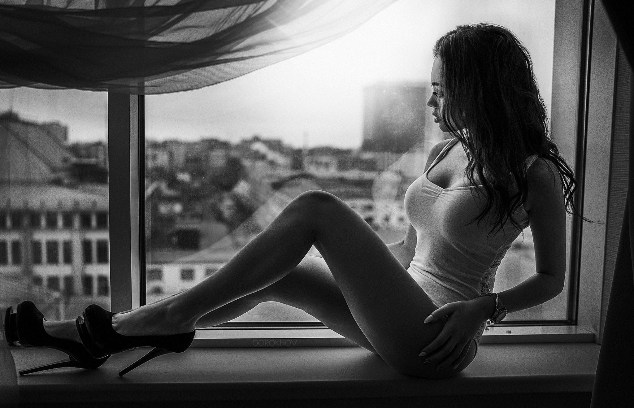 Фото Сексуальная девушка сидит на подоконнике, сексуальные ножки, каблуки, поглаживает бедро, майка, окно, черно-белая эротика, скачать картинку бесплатно