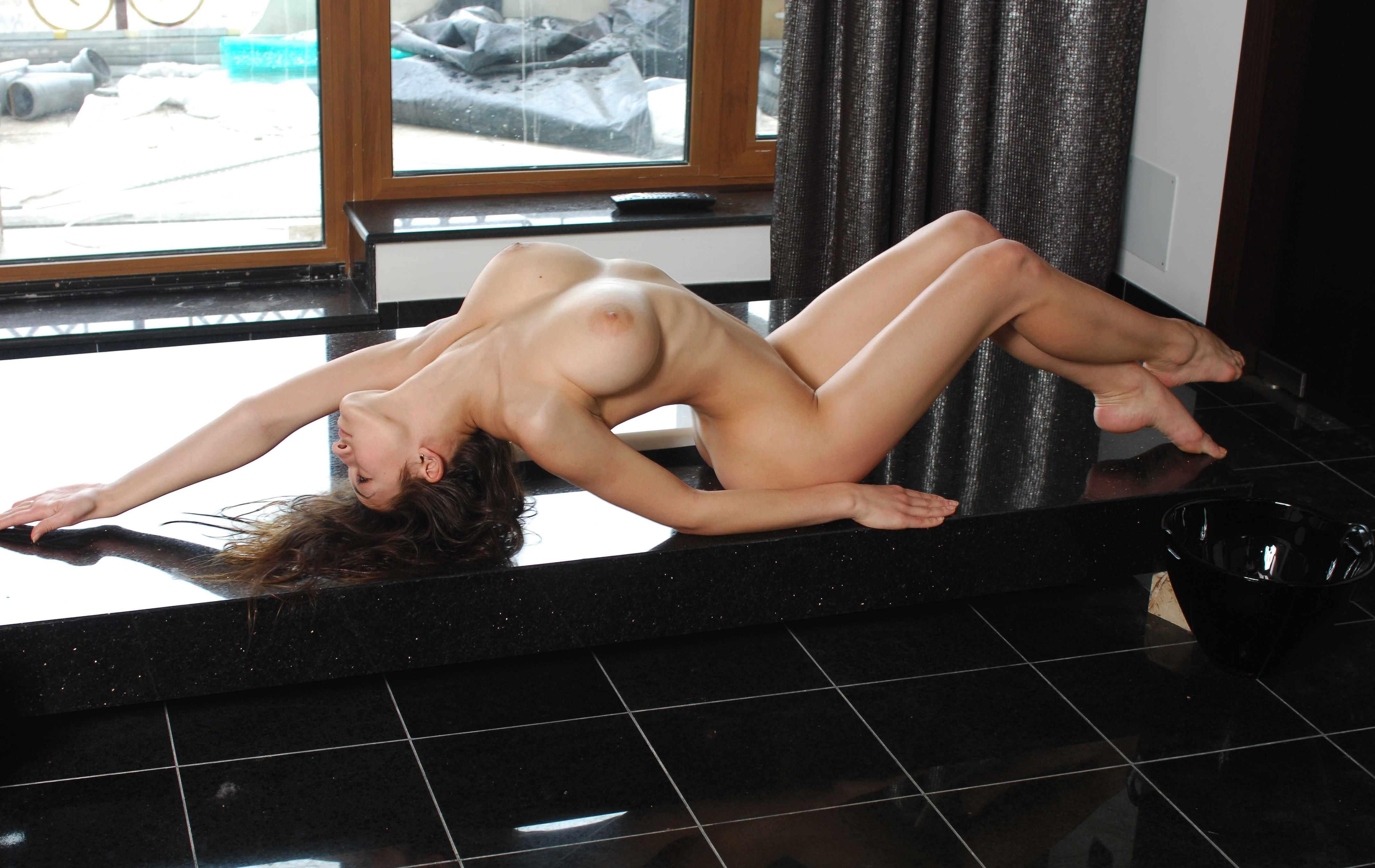 Фото Обнаженная девушка грациозно разлеглась на столе, сексуальное тело, большие красивые сиськи, скачать картинку бесплатно