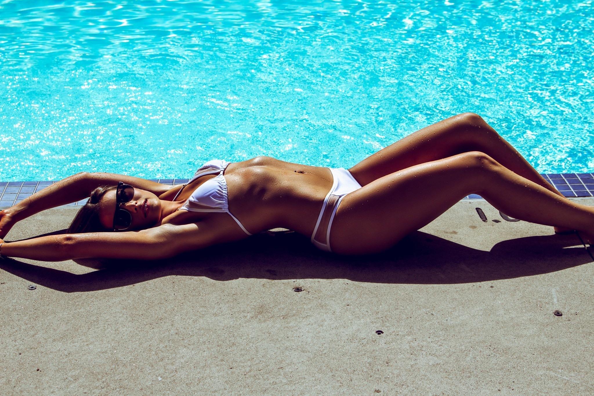 Фото Девушка в белом купальнике загорает возле бассейна, вытянувшись в струнку, скачать картинку бесплатно
