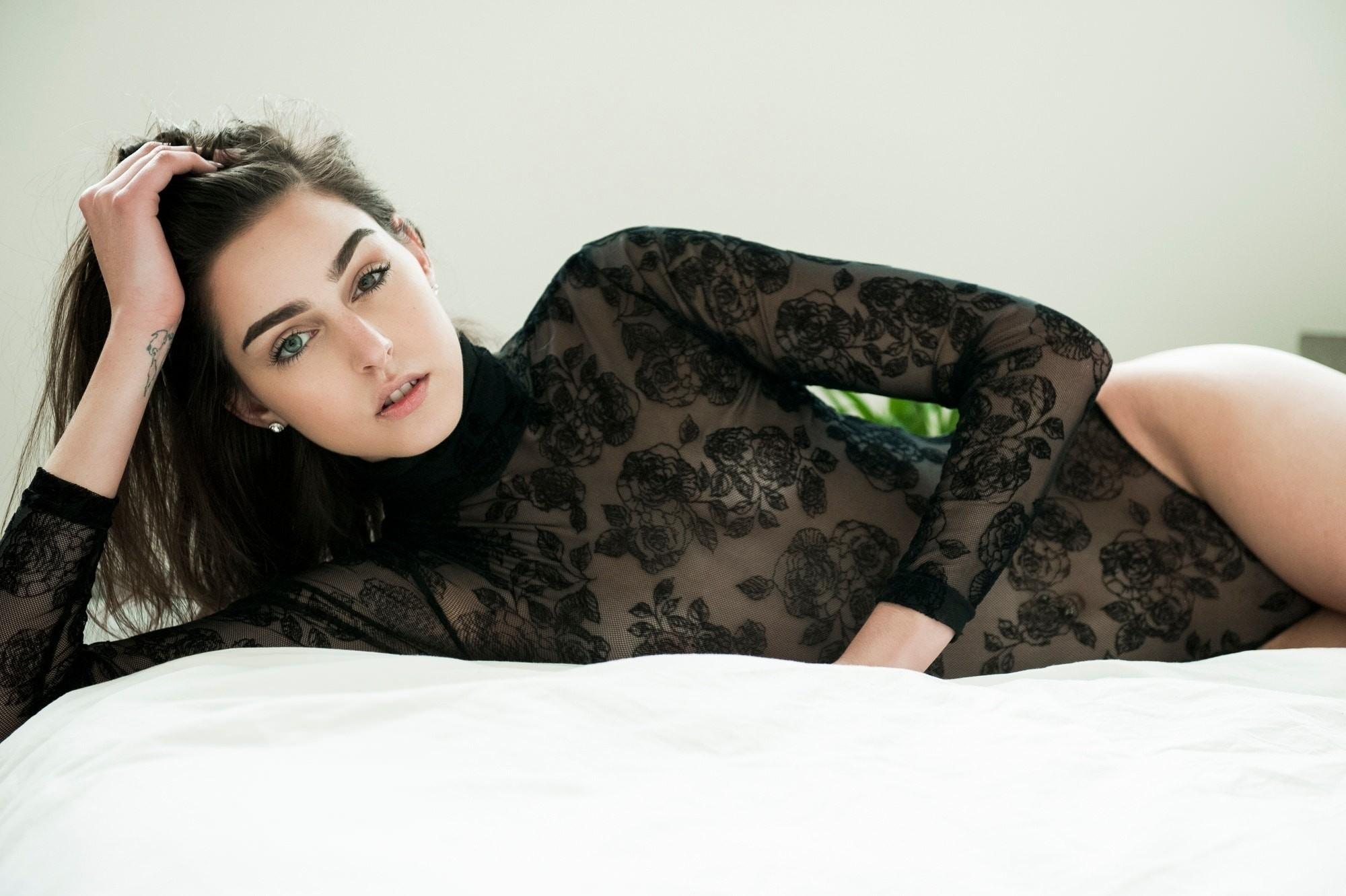 Фото Брюнетка в черном узорчатом прозрачном боди, постель, скачать картинку бесплатно