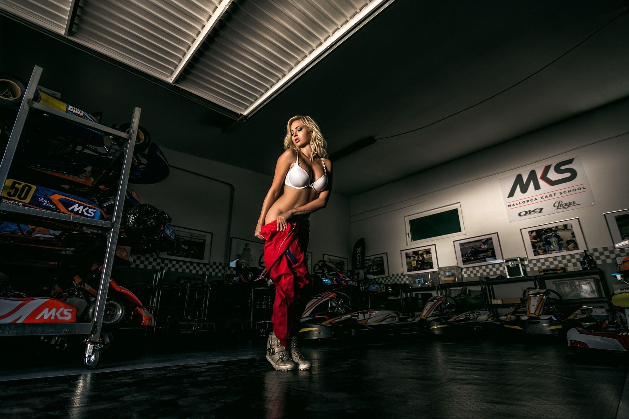 Фото Блондинка снимает спортивный красный комбинезон после гонки на формуле 1, белый лифчик, шикарная фигура, скачать картинку бесплатно