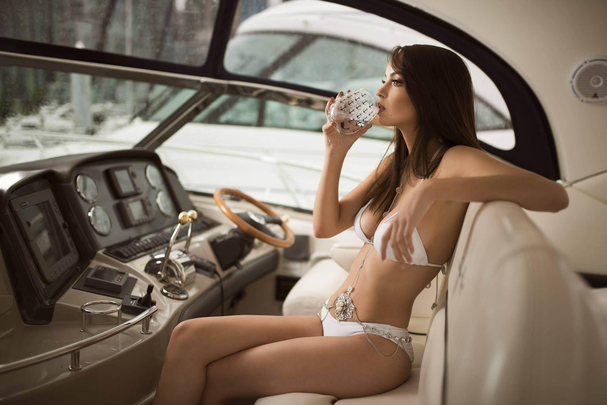 Фото Красотка в белом купальнике пьет из бокала за штурвалом яхты, скачать картинку бесплатно