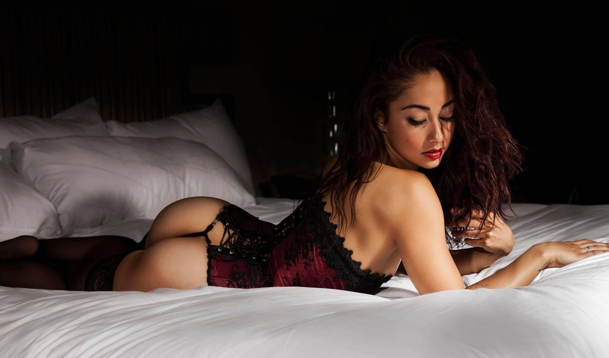 Фото Жгучая красотка в бордовом корсете, сексуальная попка, чулочки, постель, скачать картинку бесплатно