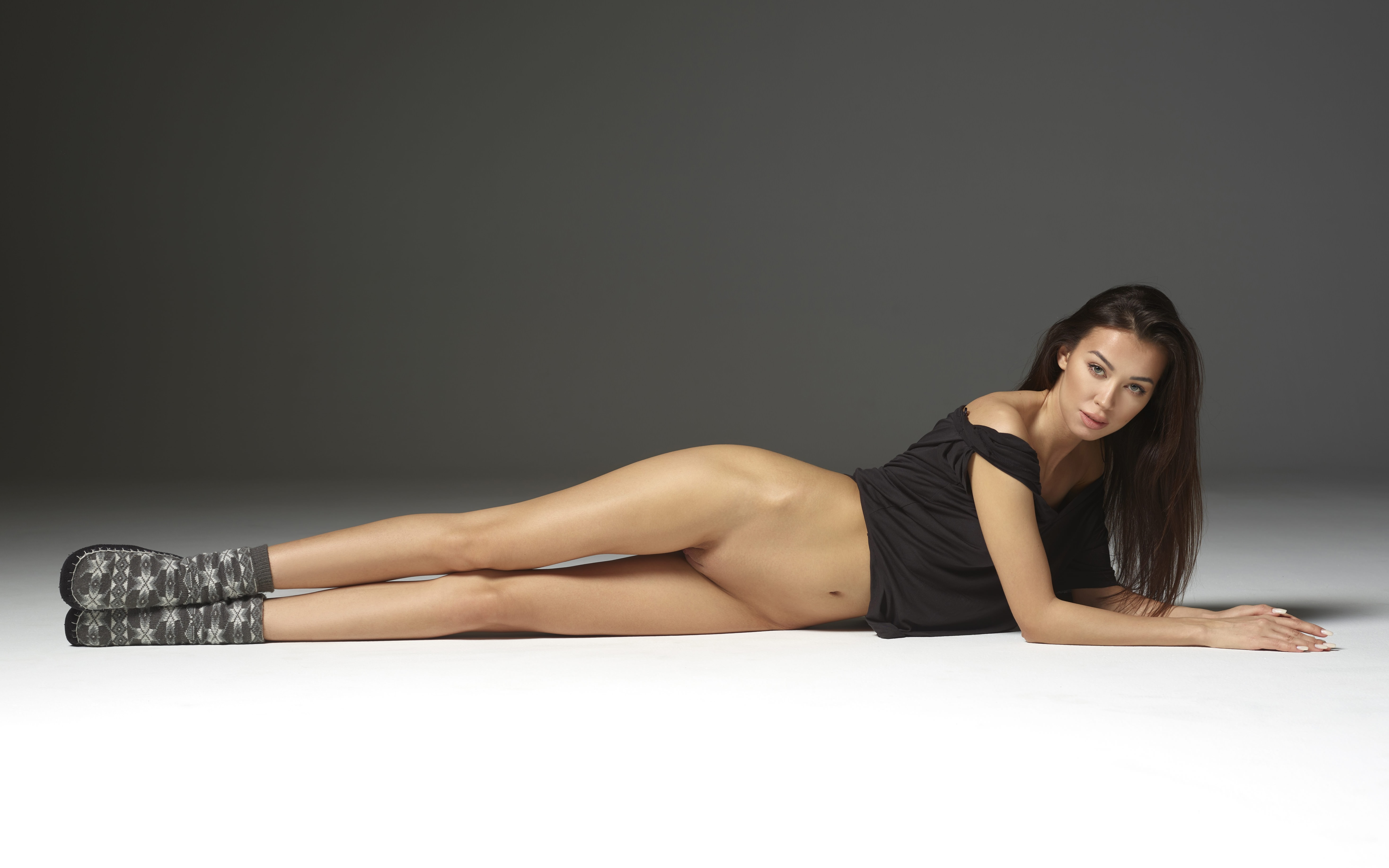 Фото Девушка без трусиков вытянулась в струнку на полу, длинные ножки, угги, красивая брюнетка в черном топике, скачать картинку бесплатно