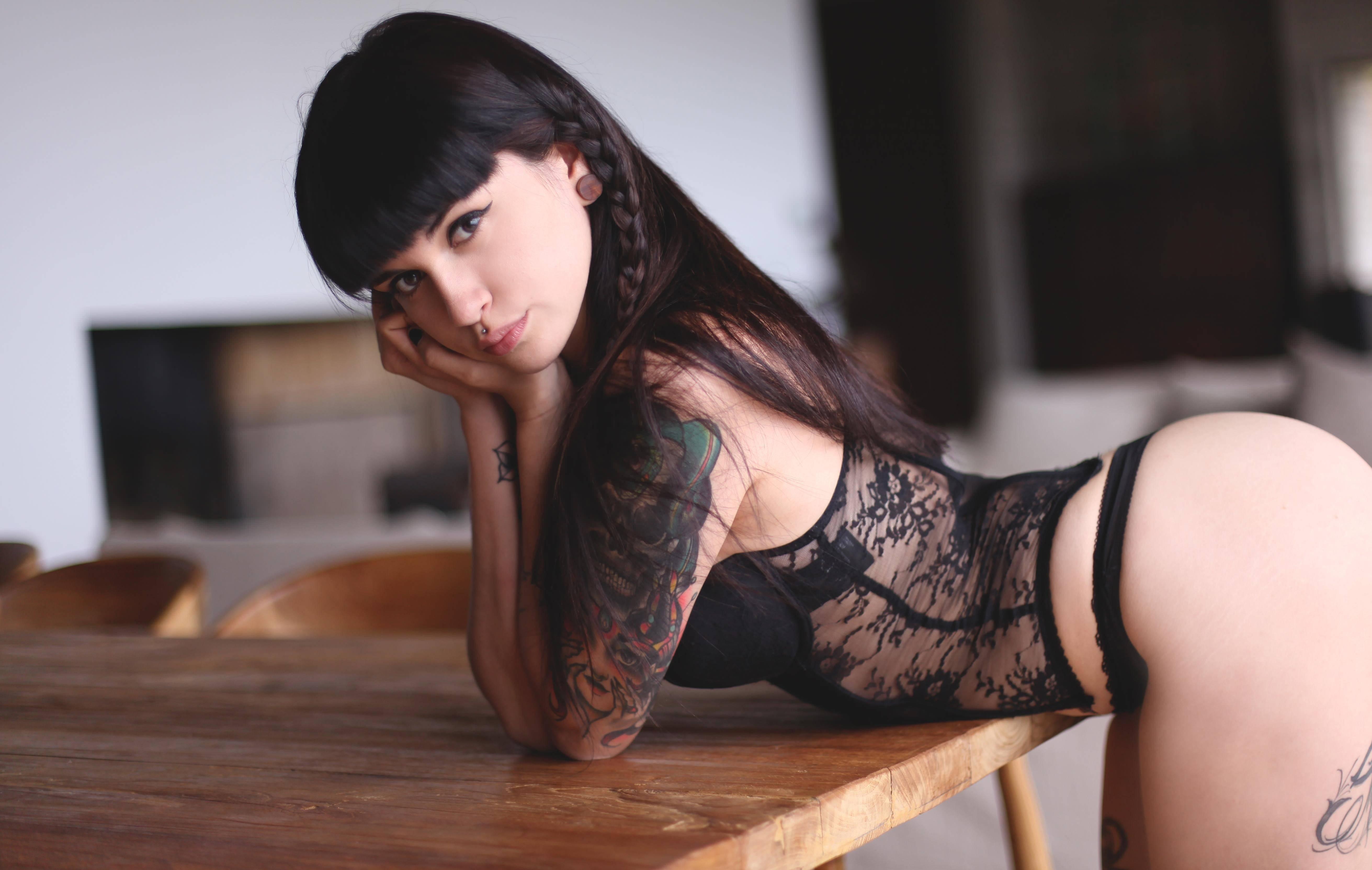 Фото Красивая брюнетка с косами в черной ночнушке наклонилась над столом, цветное тату на руке, скачать картинку бесплатно