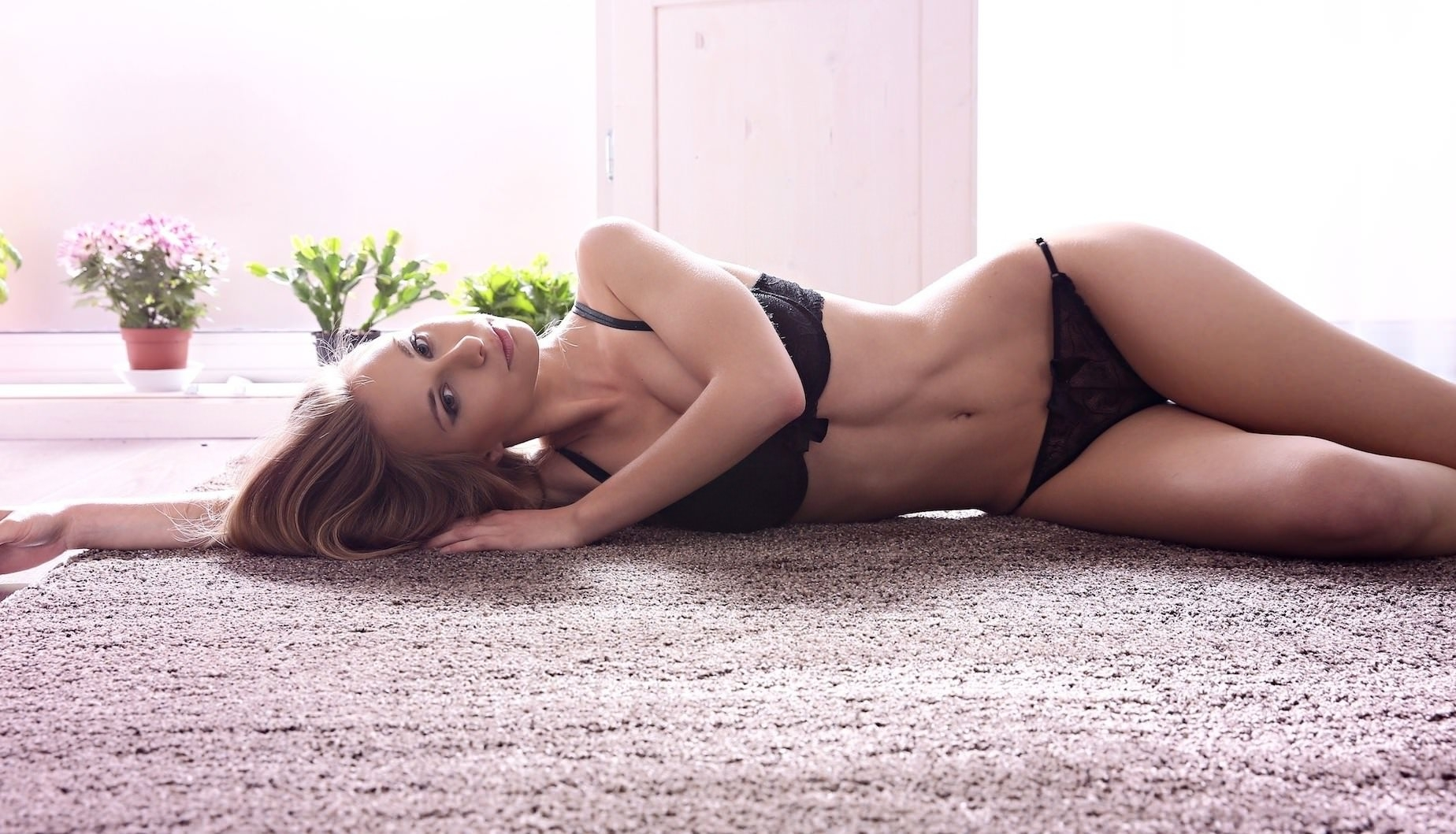 Фото Сексуальная молодая девушка в черном нижнем белье лежит на ковре, скачать картинку бесплатно