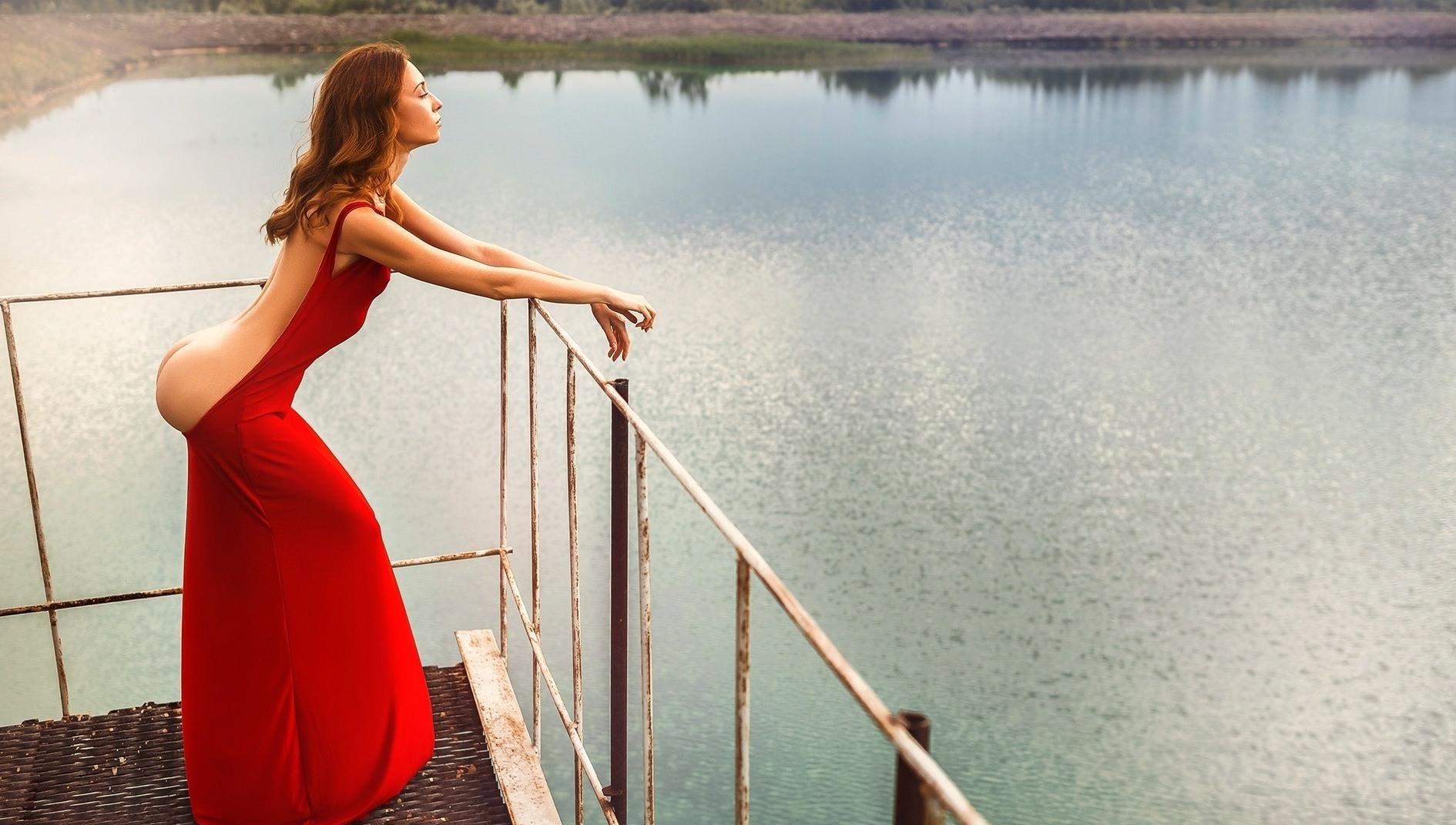 Фото Девушка в красном платье любуется на озеро, вытащила попку из платья и оттопырила назад, скачать картинку бесплатно
