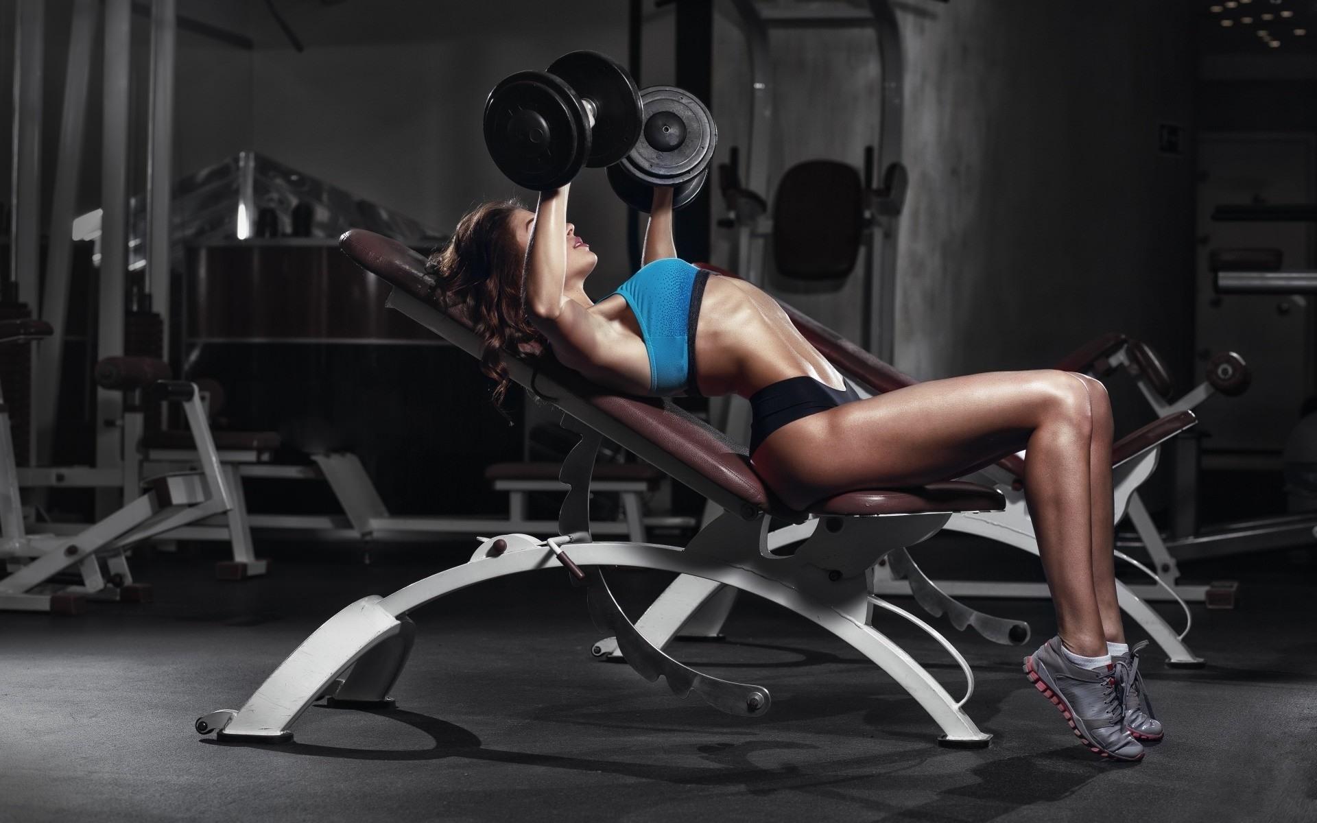 Фото Девушка в тренажерном зале, идеальная фигура, жим гантелей на наклонной скамье, сексуальное спортивное женское тело, скачать картинку бесплатно