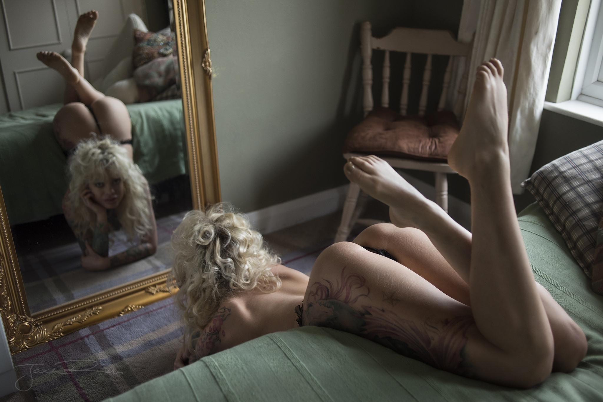 Фото Кудрявая блондинка в стрингах легла перед зеркалом, тату, скачать картинку бесплатно