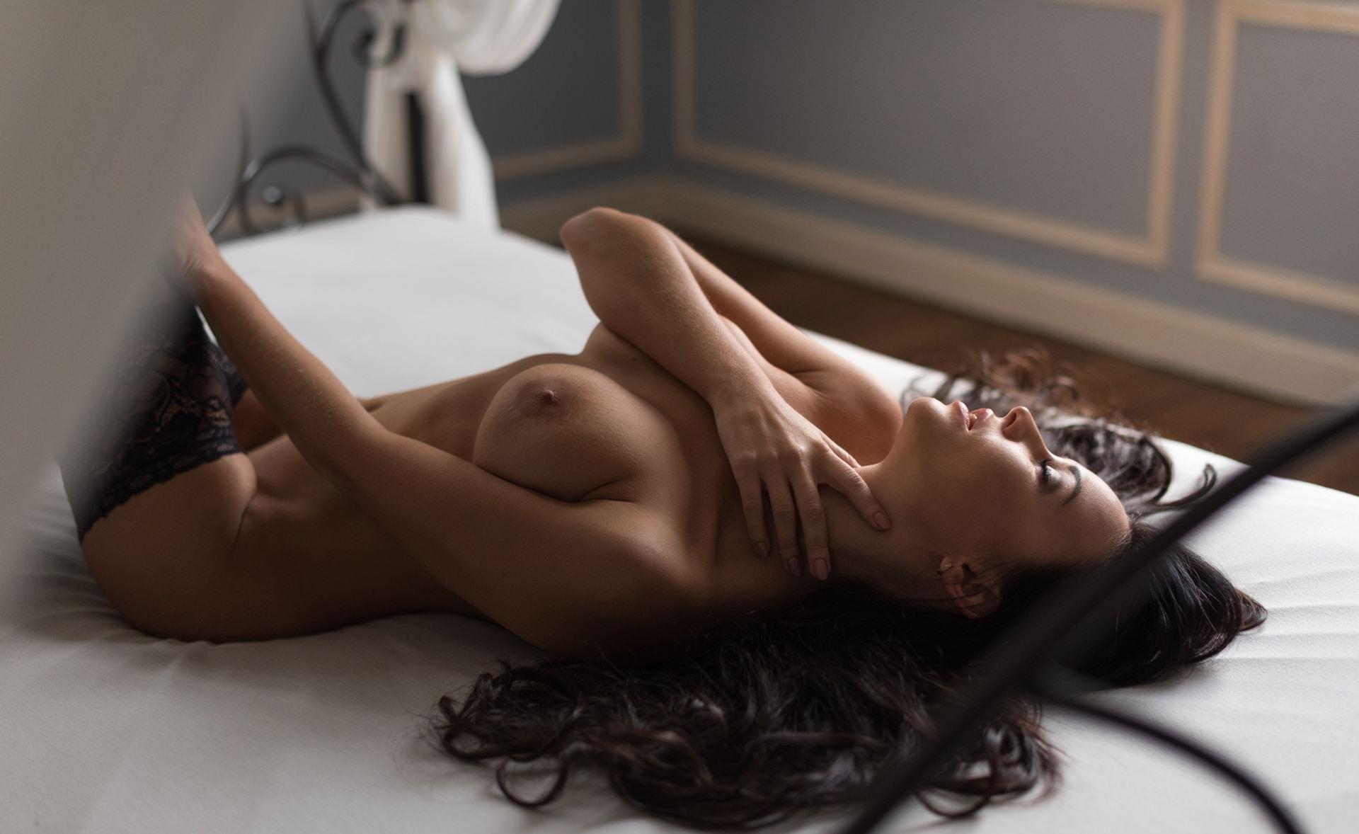 Фото Брюнетка ласкает шею, голые сиськи, чулки, пышные волосы, постель, скачать картинку бесплатно