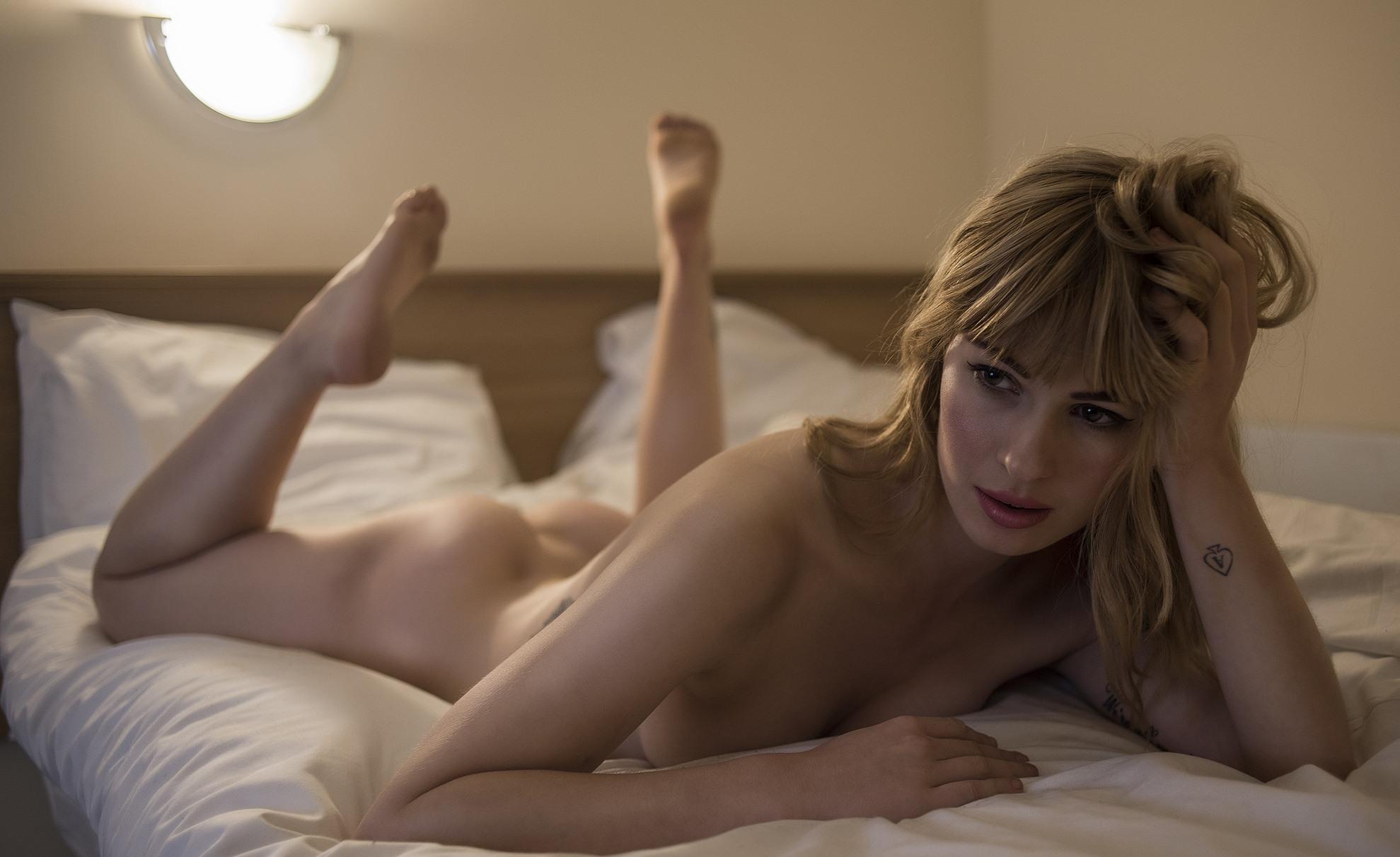 Фото Голая девушка, задумавшись лежит в постели, виляя ножками, скачать картинку бесплатно