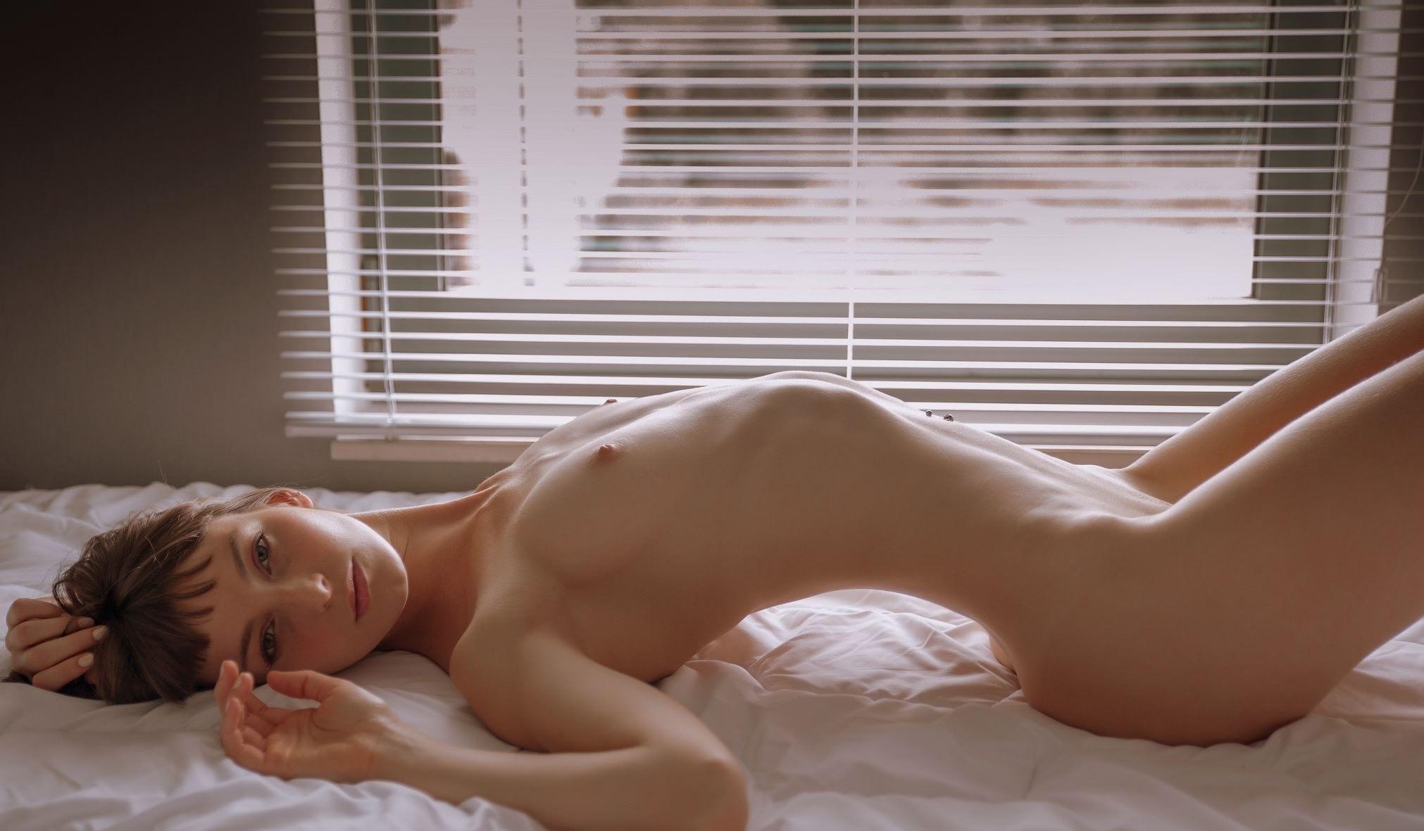 Фото Голая девушка на кровати, согнула спинку, жалюзи, скачать картинку бесплатно