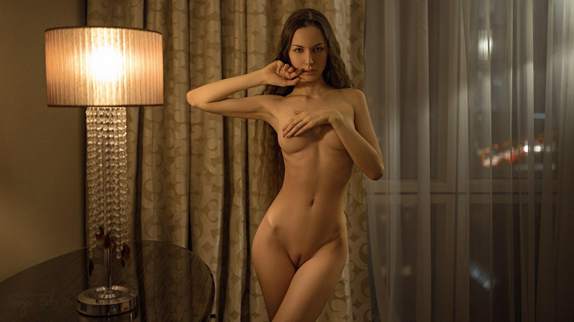 Фото Голая девушка эротично встала в комнате, прикрыла грудь рукой, пальцем водит по губам, лампа, скачать картинку бесплатно